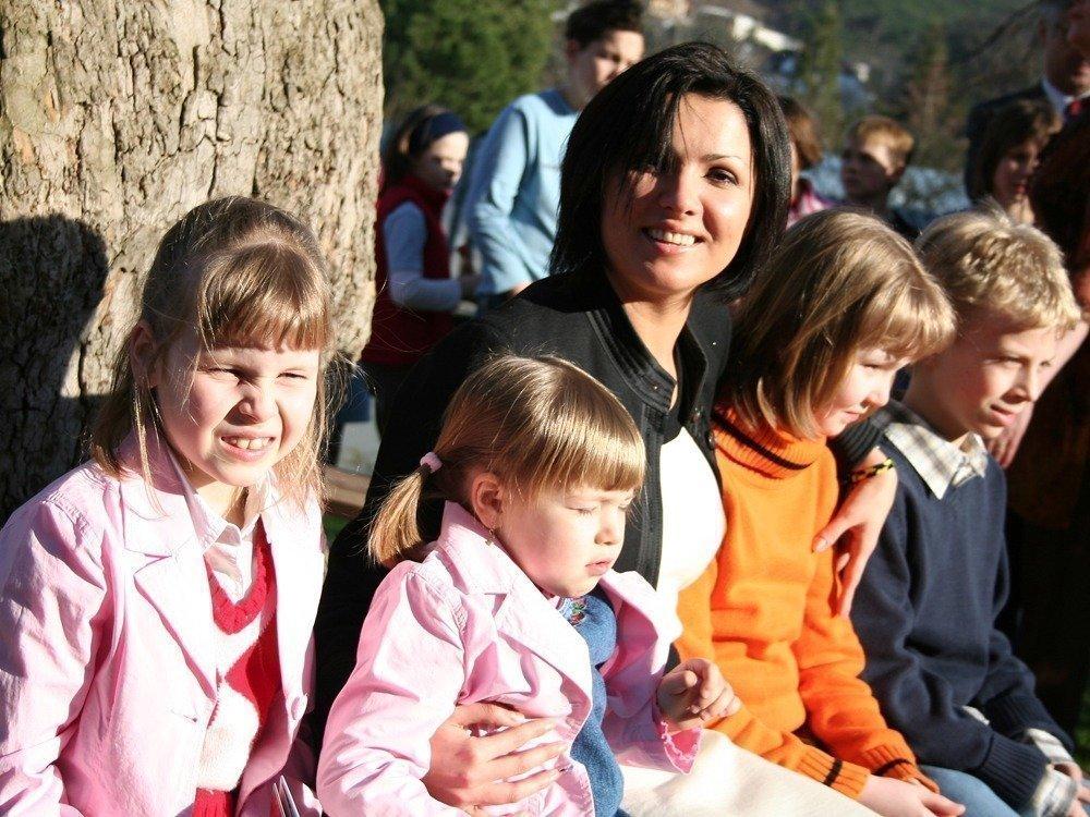Anna Netrebko mit Kindern vor einem Baum.