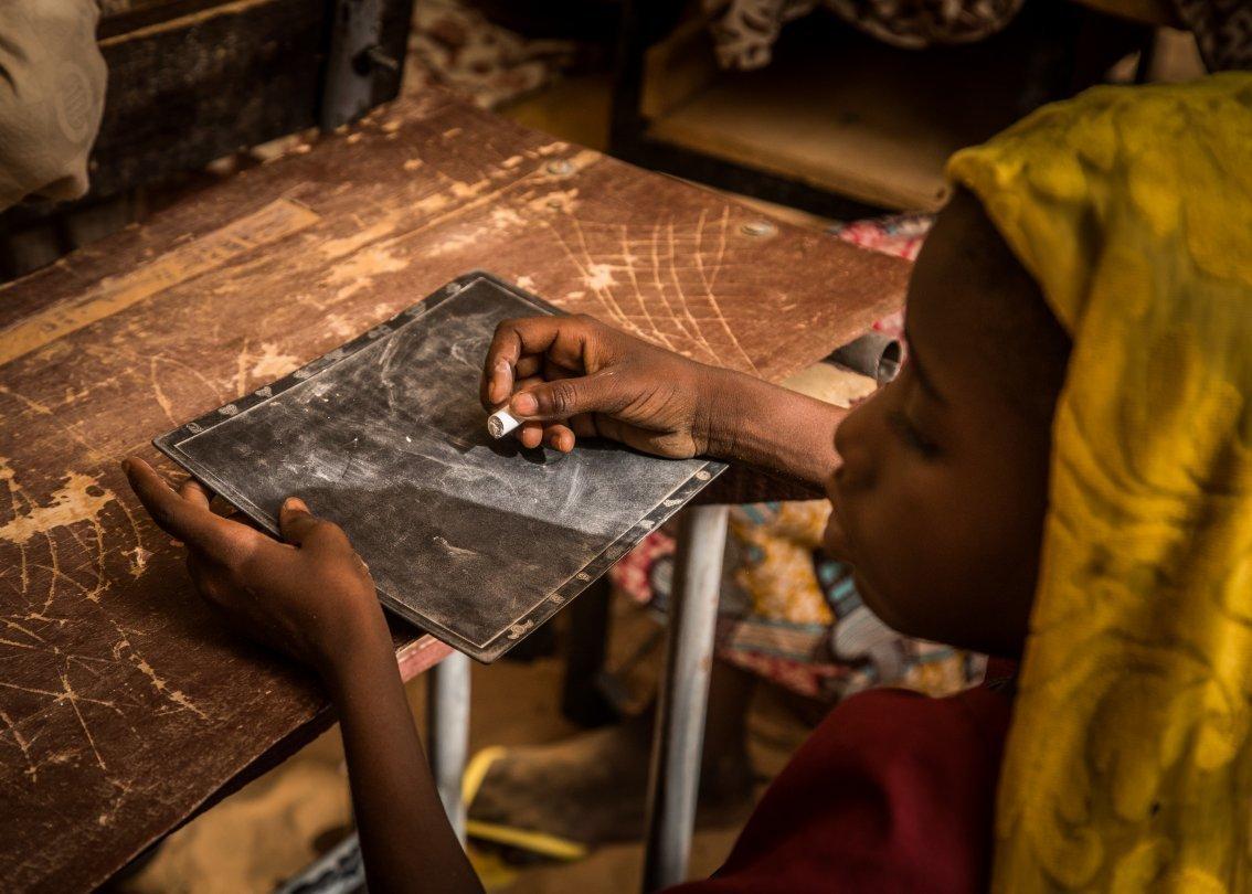 Mädchen schreibt auf einer Tafel.