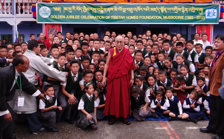 Dalai Lama vor einer Gruppe Kinder.