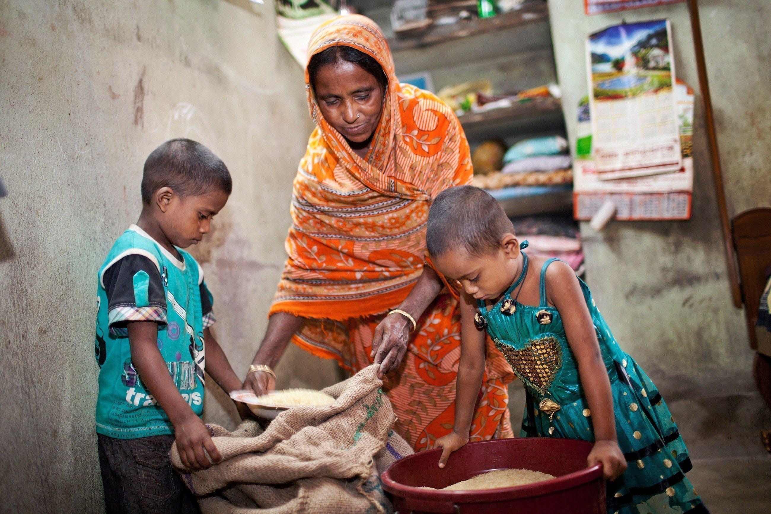 Zwei Kinder blicken in Säcke und Behälter mit Körnern.