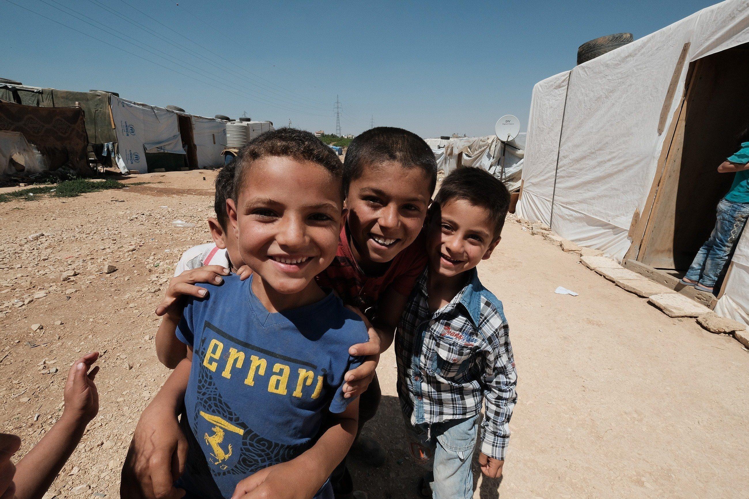 Drei syrische Jungs lächeln sich umarmend in die Kamera.