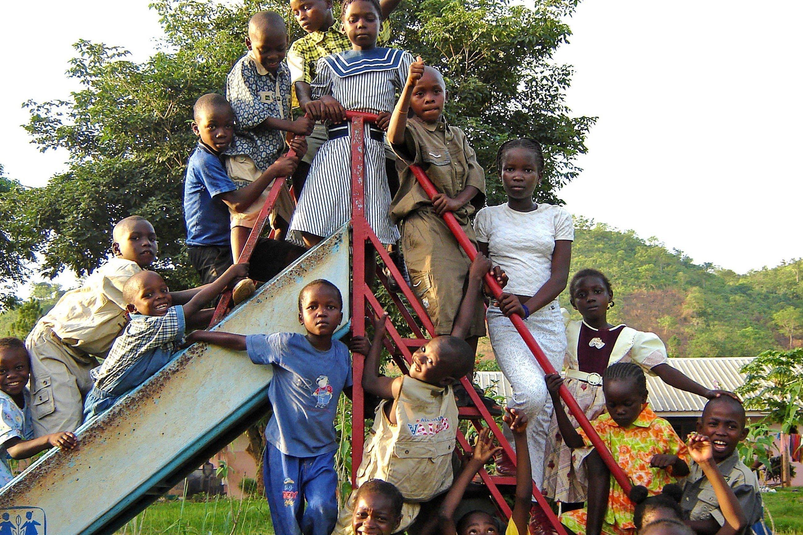 Eine Gruppe von Kindern steht auf dem Geländer einer Rutsche.