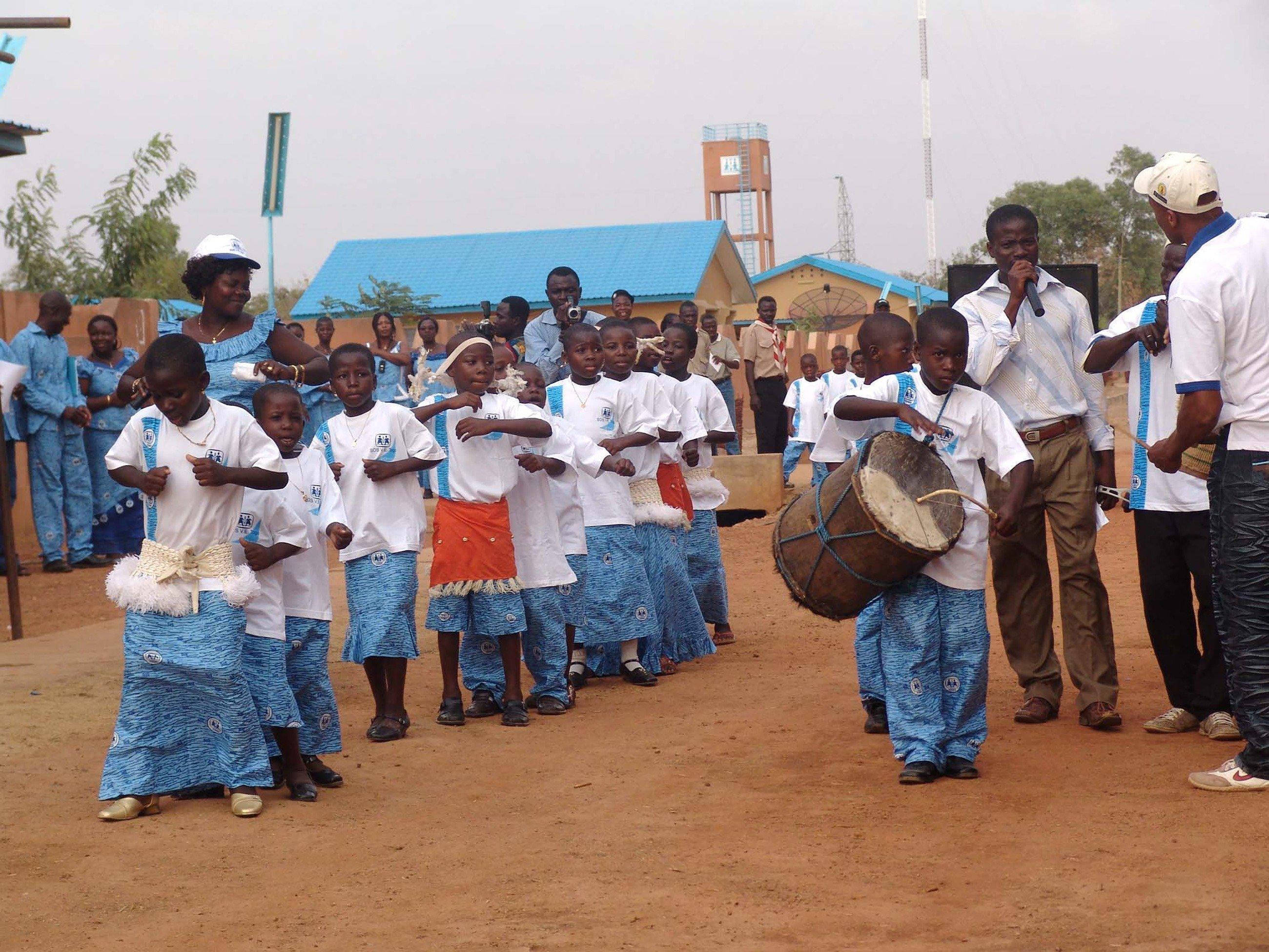 Mehrere Kinder mit der selben Uniform spielen auf Musikinstrumenten.