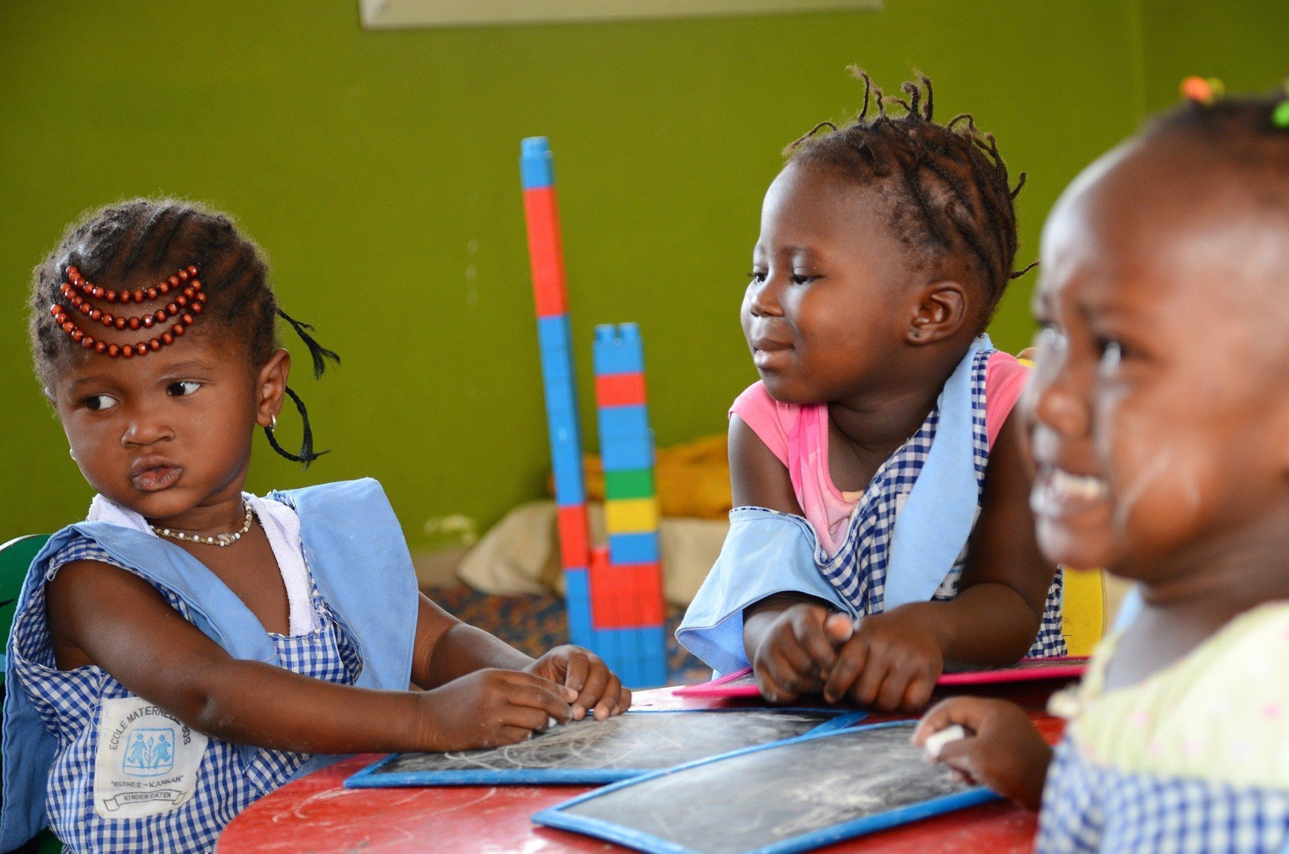 Drei kleine Mädchen sitzen an einem Tisch und spielen.