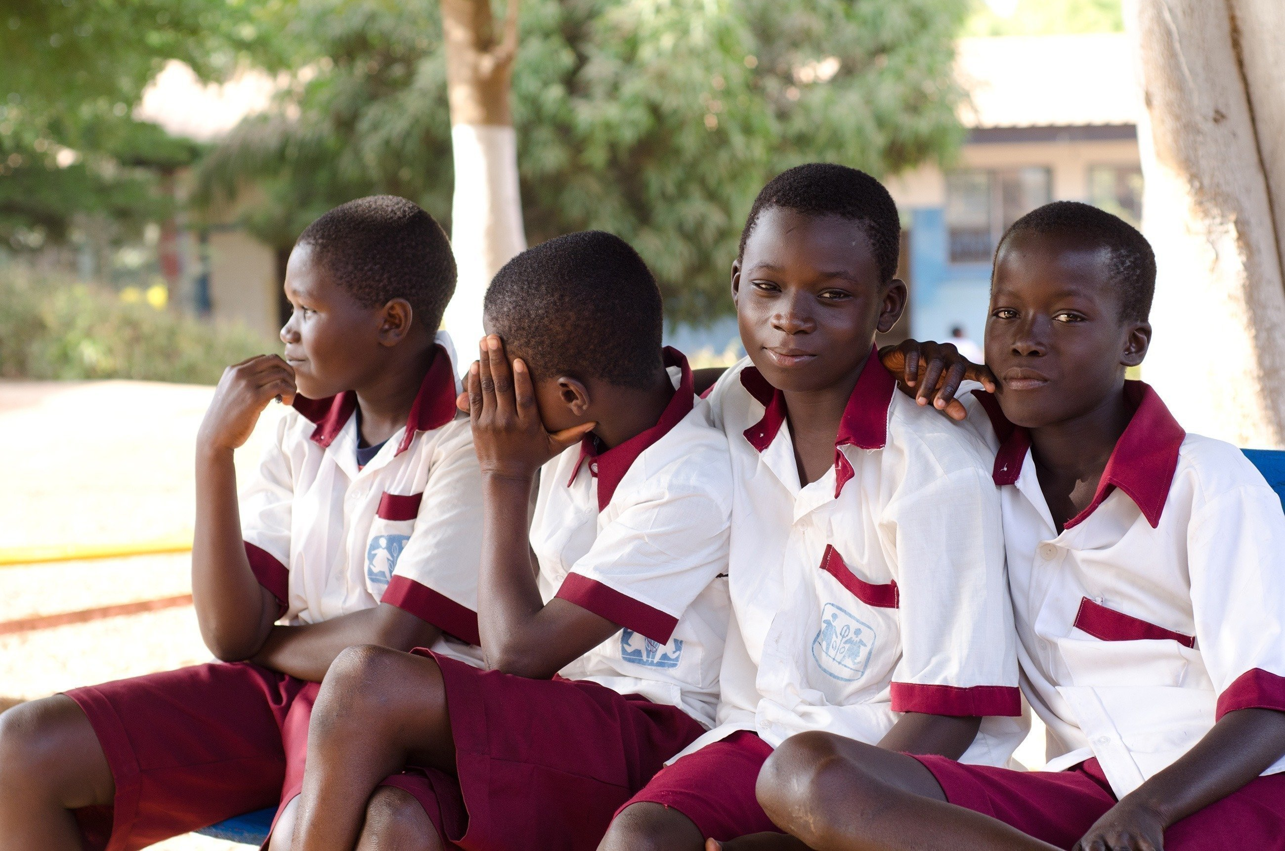 Vier Jungen sitzen in Schuluniform auf einer Bank.