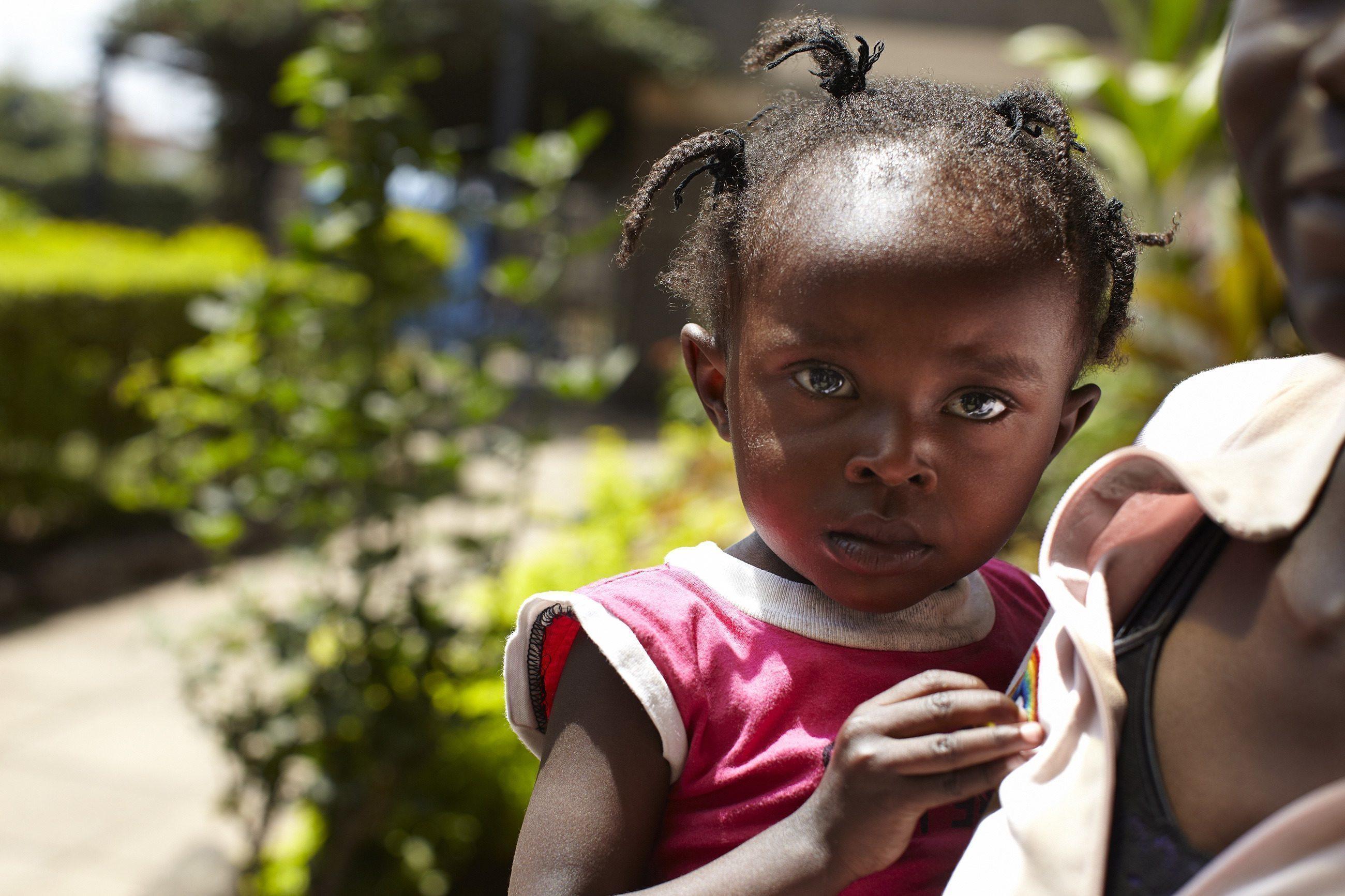 Ein Mädchen auf dem Arm einer SOS-Kinderdorf Mutter.
