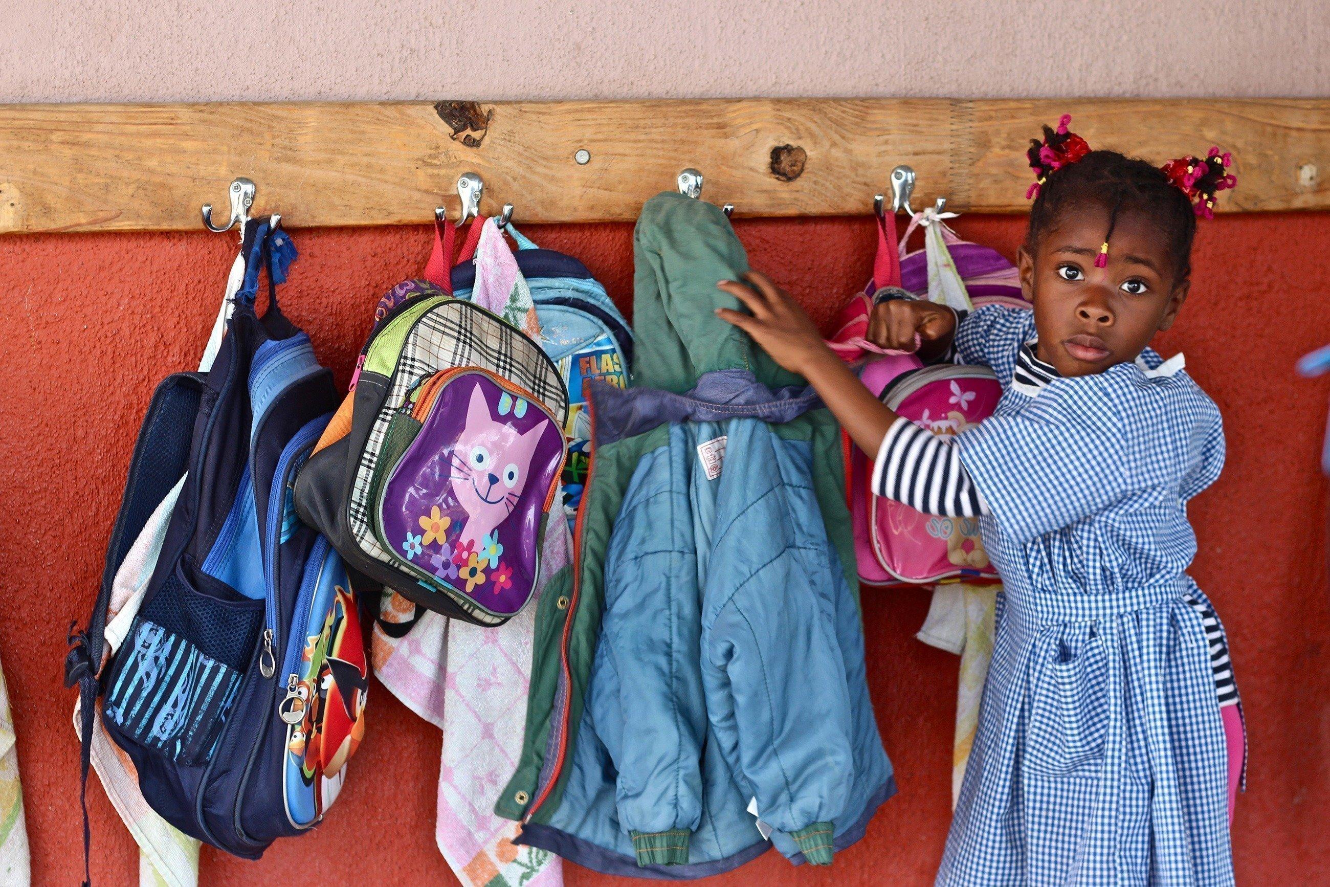 Ein Mädchen in einem Kleid sucht etwas in ihrem Rucksack.