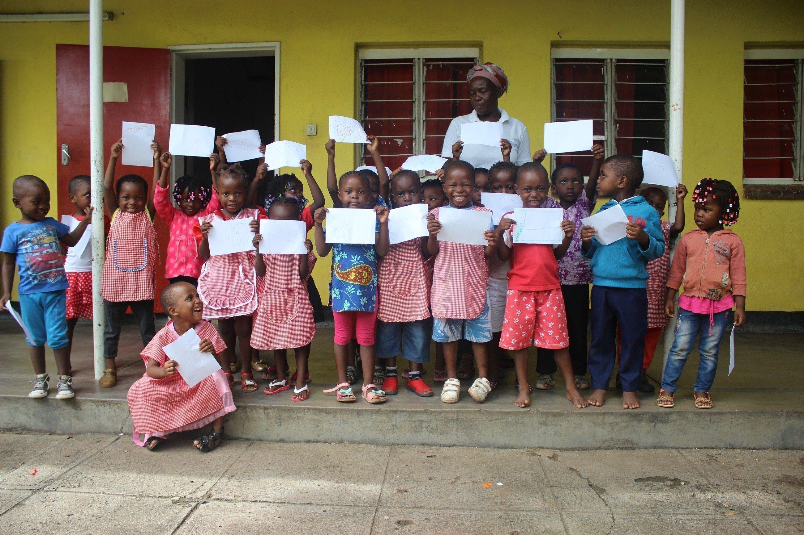 Eine Gruppe von Kindern steht mit Bildern in der Hand vor einem Haus.