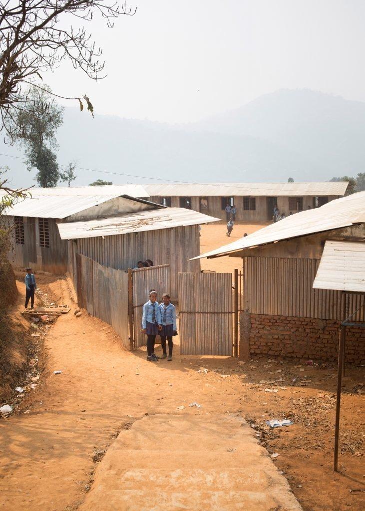 Zwei Schulmädchen vor einer Schulanlage.