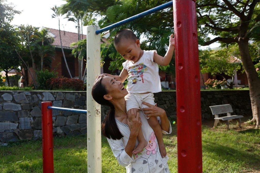 Kleines Kind am Klettergerüst mit seiner Mutter.