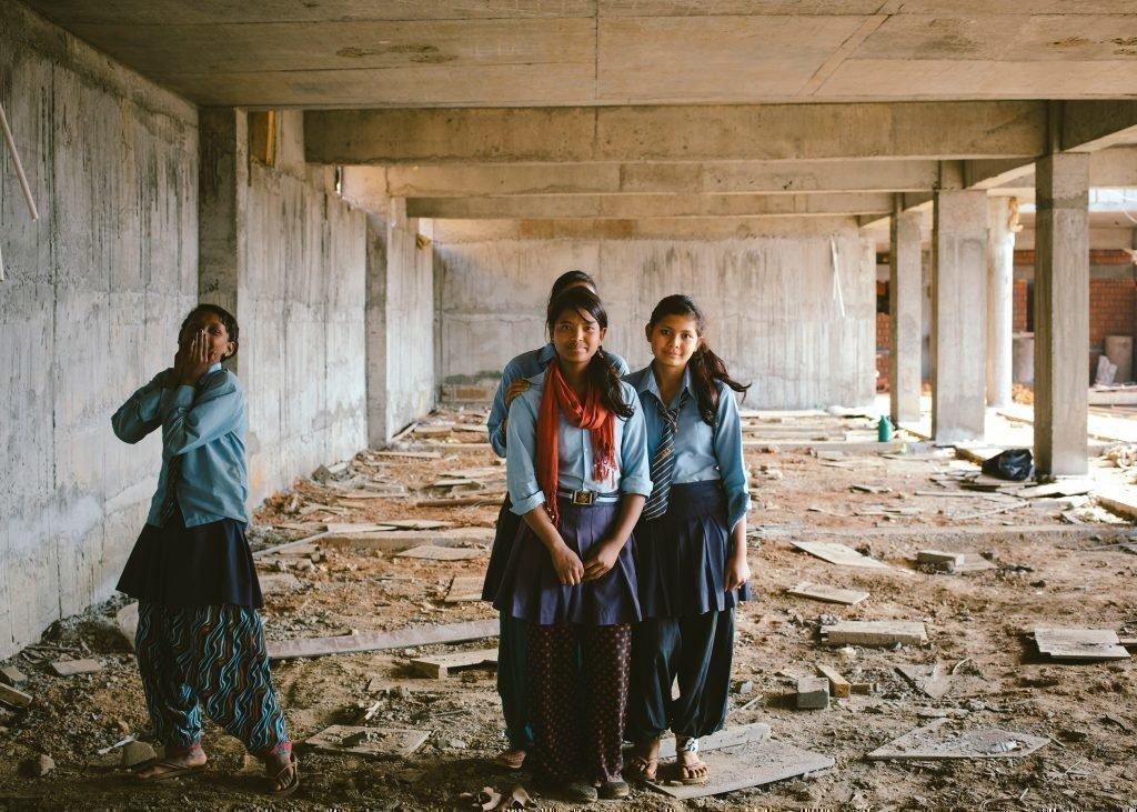vier Mädchen in den Trümmern eines Hauses. lachen.
