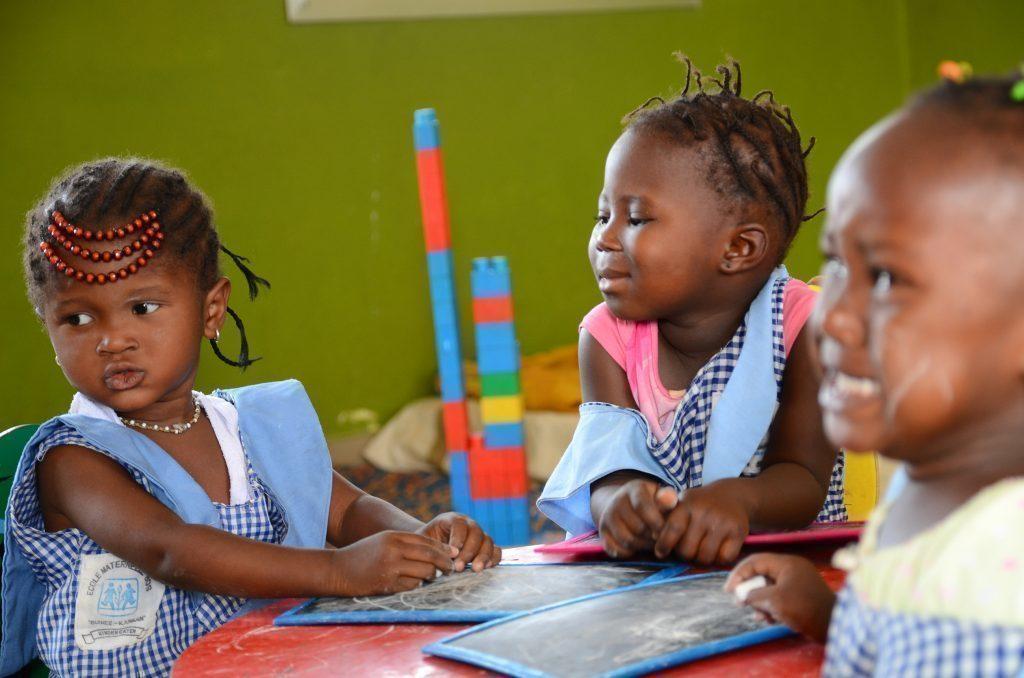 Drei spielende Mädchen an einem Tisch.