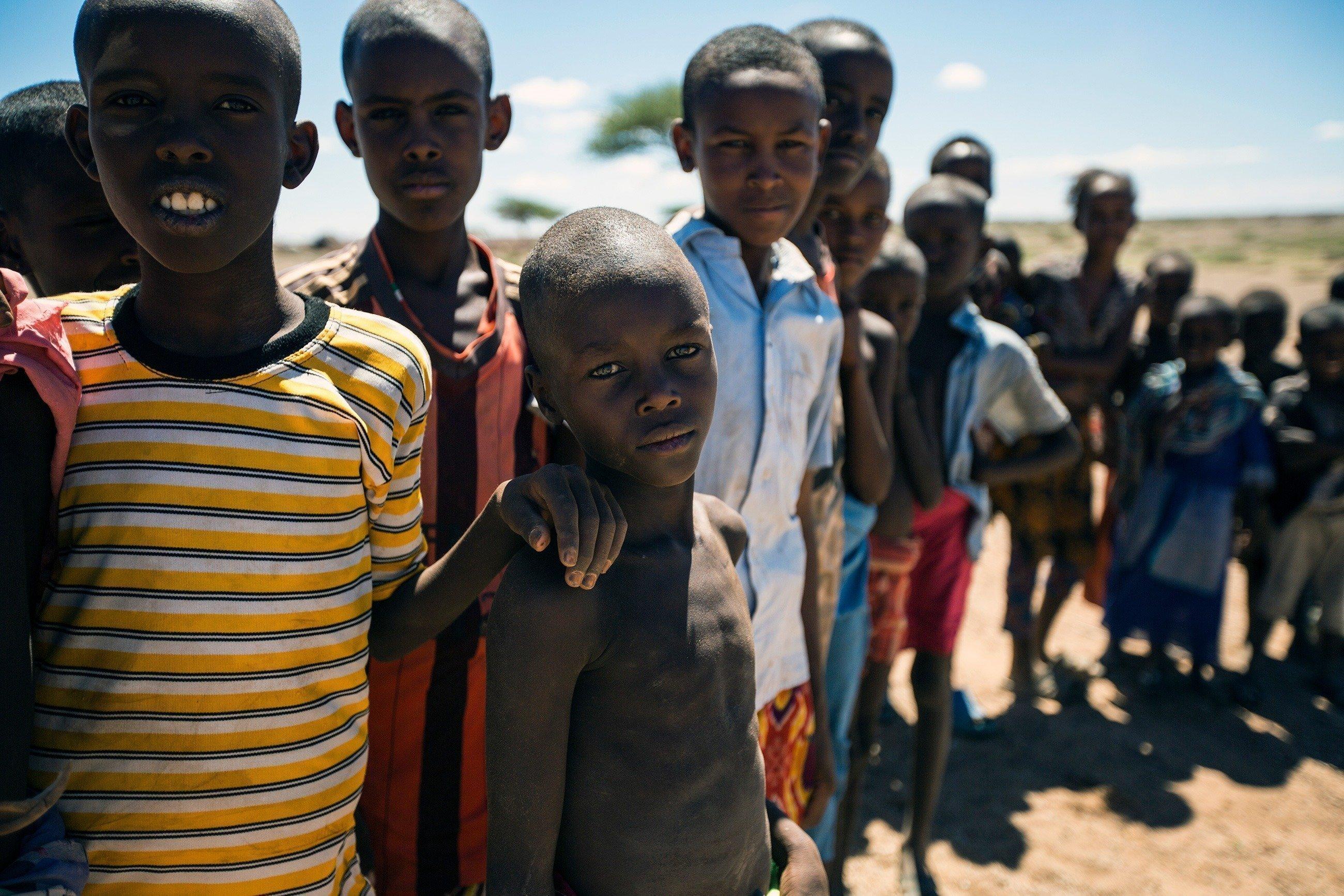 Mehrere Kinder stehen in einer Reihe und schauen in die Kamera.