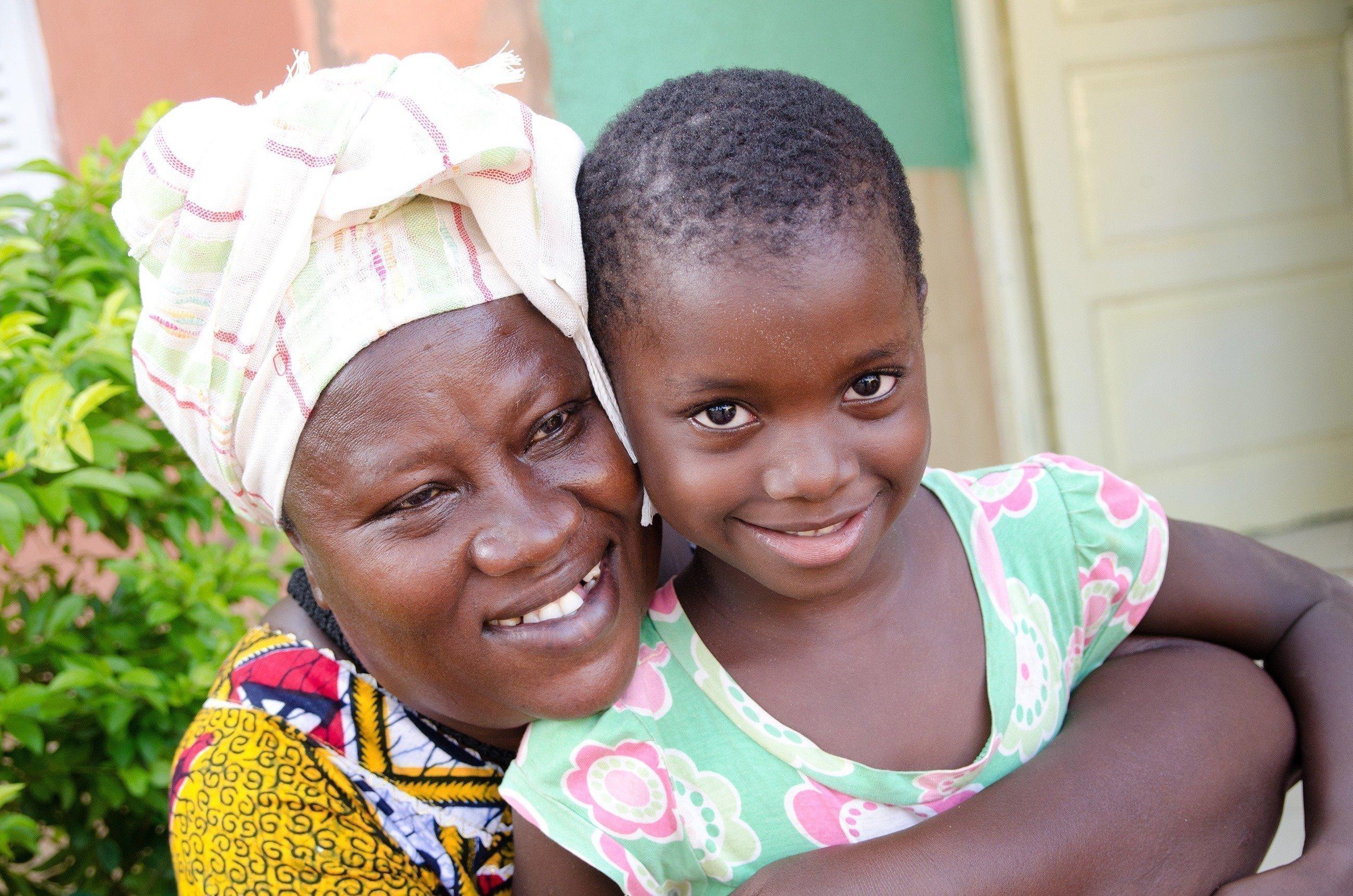 Eine SOS-Kinderdorf Mutter umarmt liebevoll ein kleines Mädchen.
