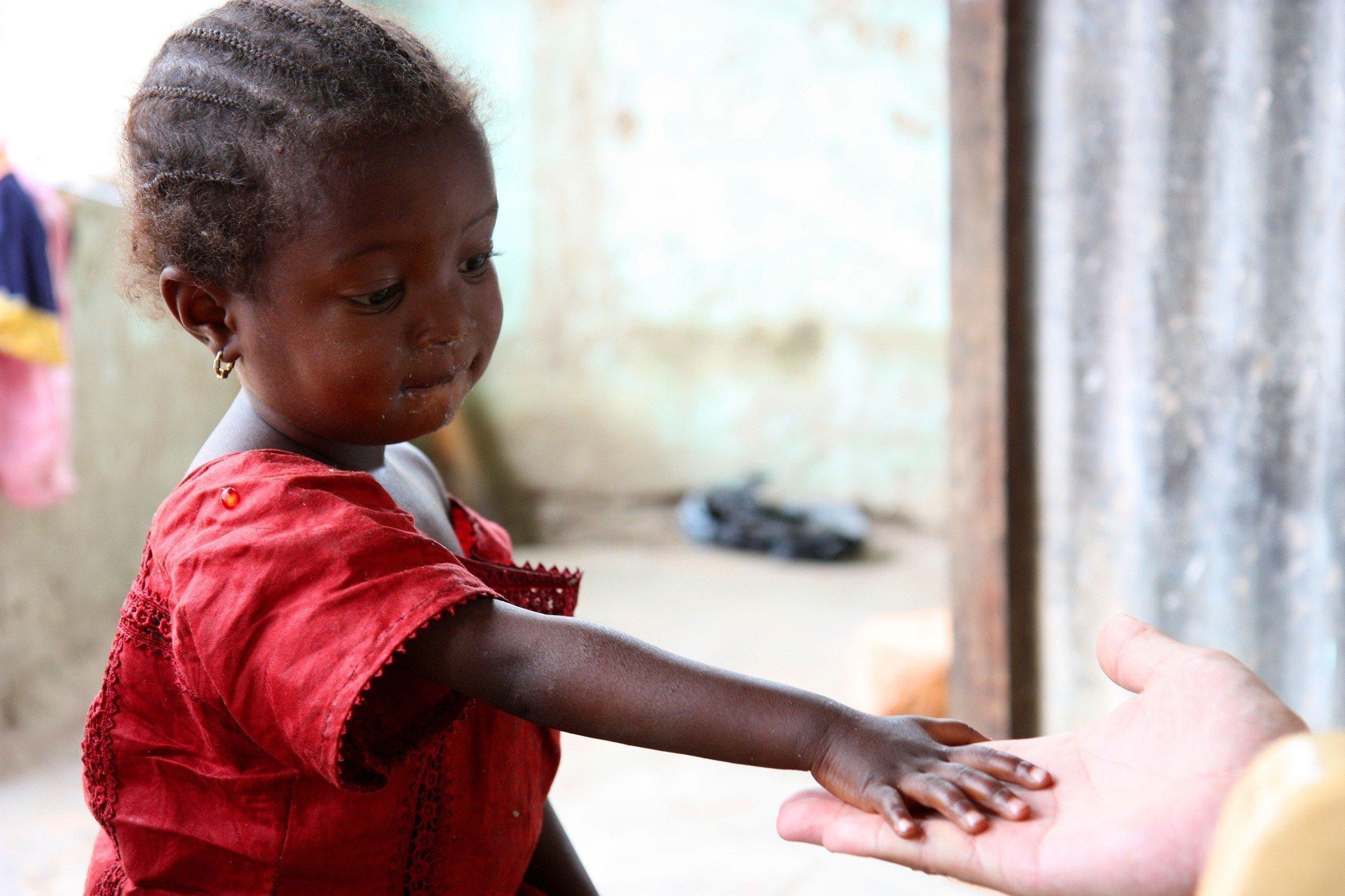 Ein kleines Mädchen reicht ihre Hand einem Erwachsenen.