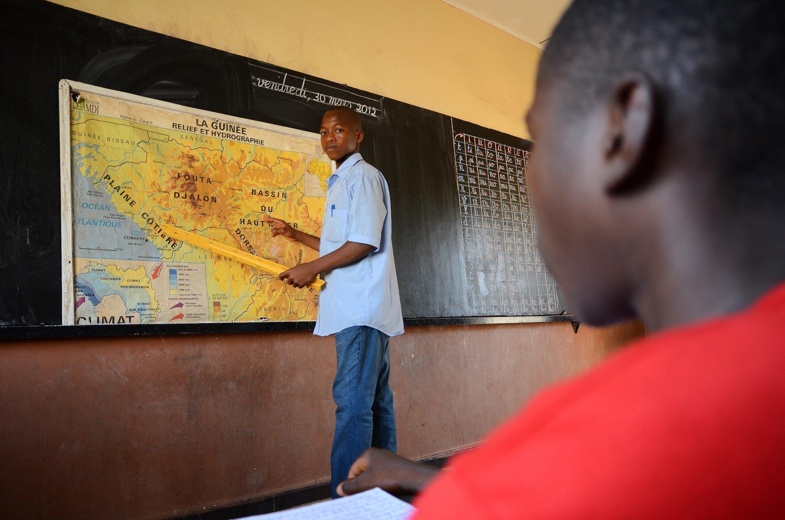 Ein SOS-Kinderdorf Lehrer erklärt seinen Schülern an der Tafel den Unterrichtsstoff.