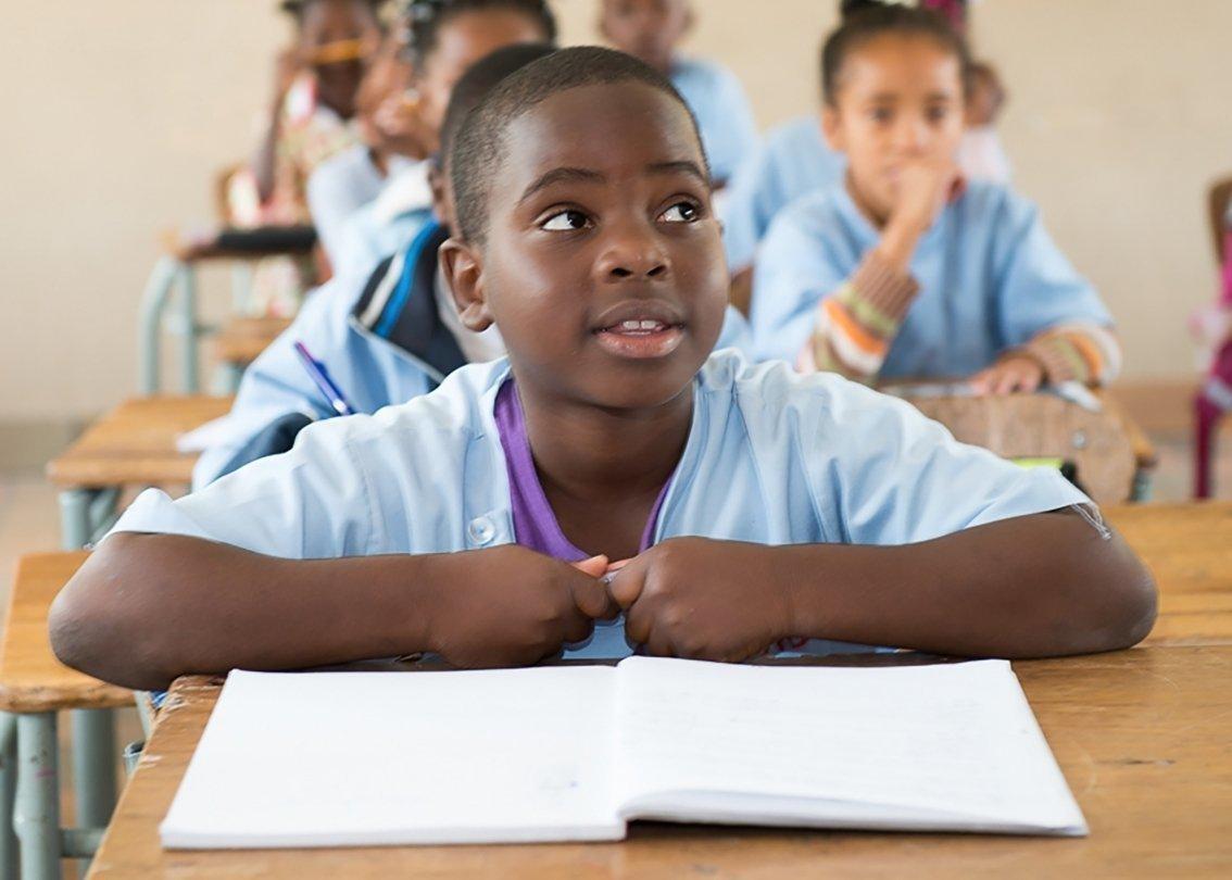 Afrikanisches Kind sitzt in SOS-Kinderdorf-Schule am Tisch.