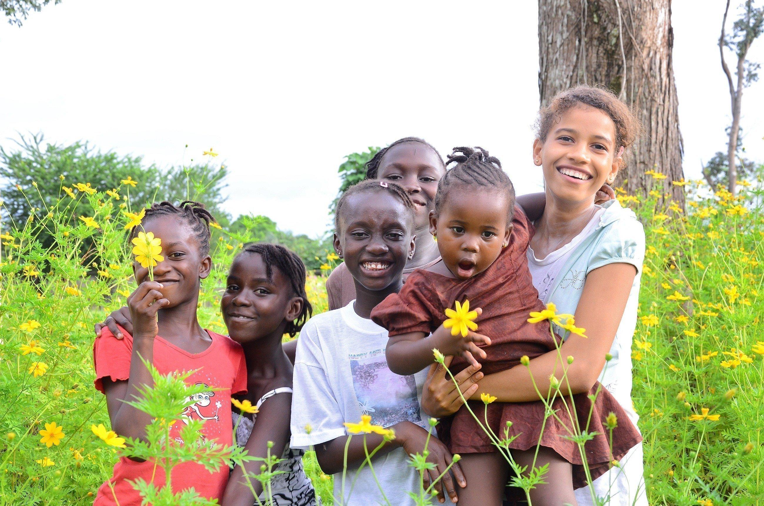 Mehrere Kinder stehen lachend auf einer Wiese.