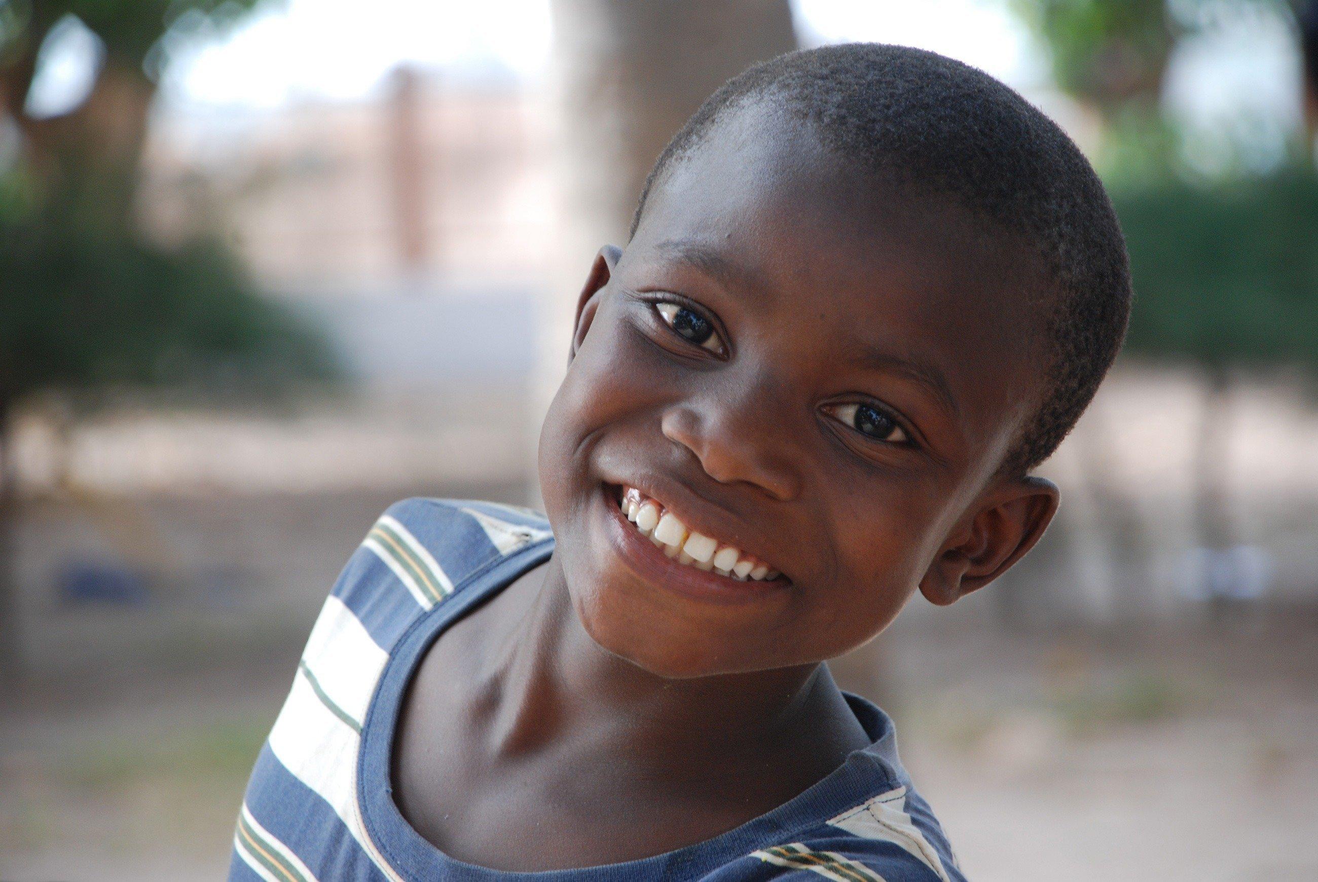 Ein fröhlicher Junge grinst in die Kamera.