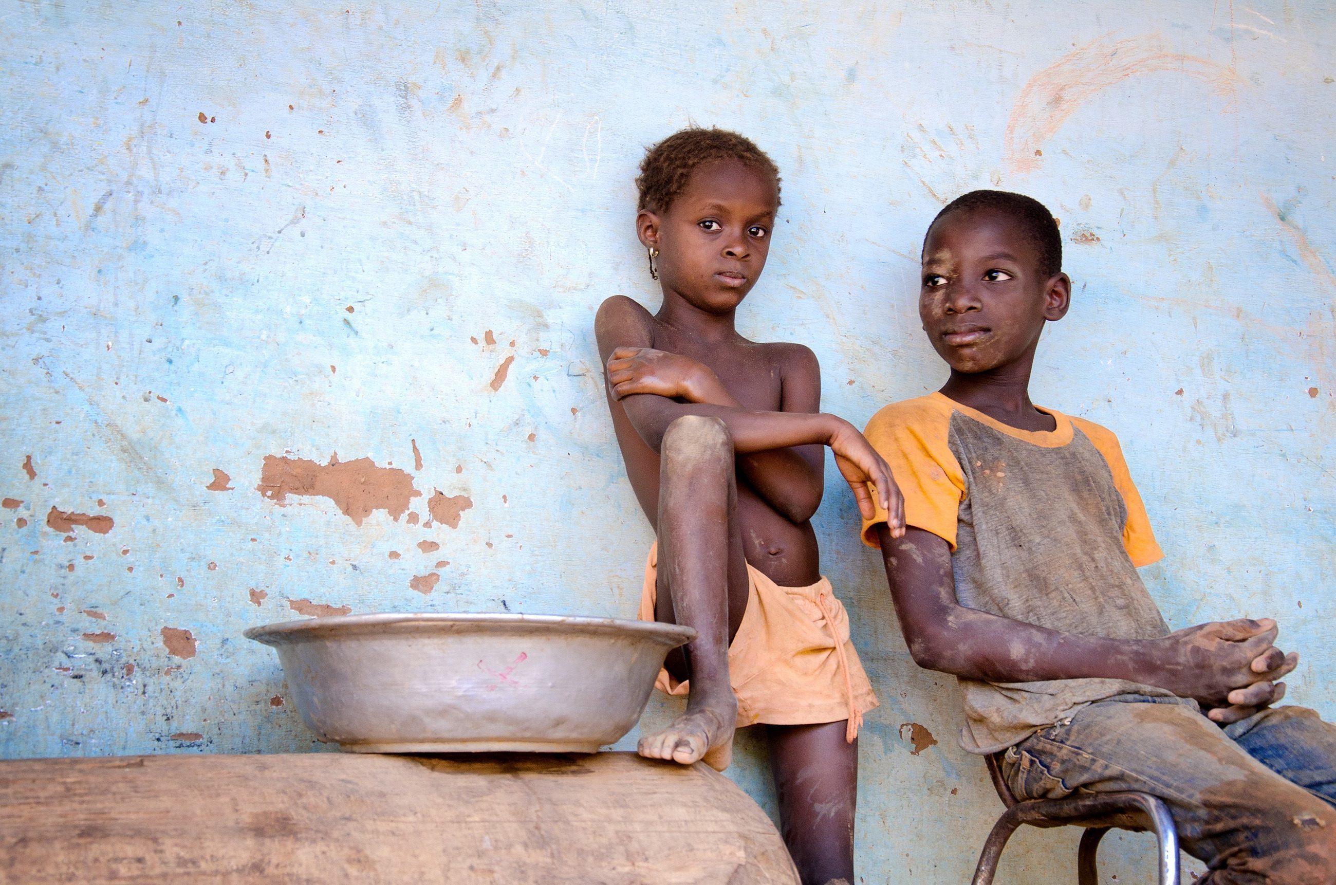 Zwei ärmlich aussehende Jungen lehnen an einer blauen Wand.