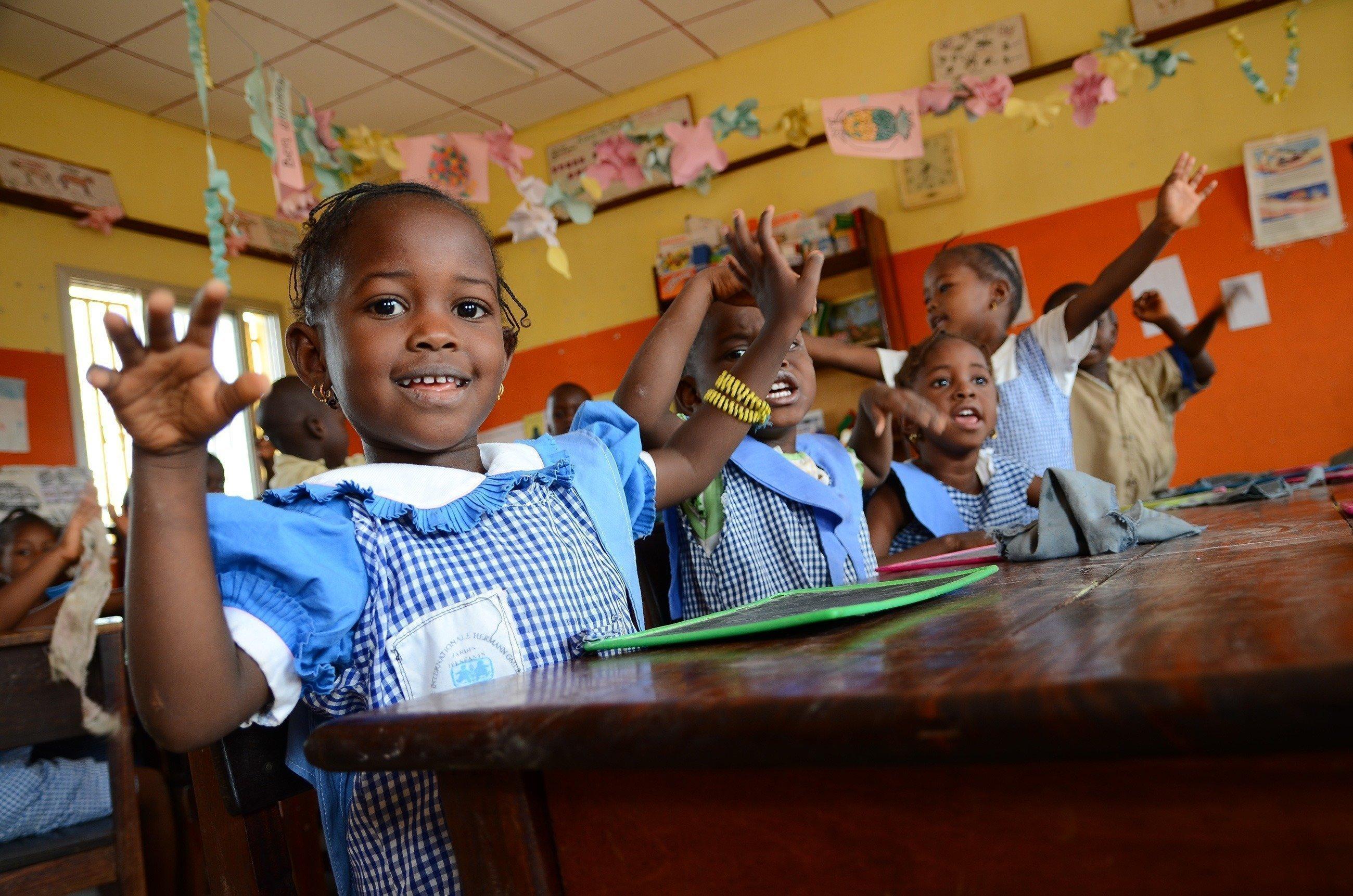 Mehrere kleine Kinder in Schuluniform freuen sich.