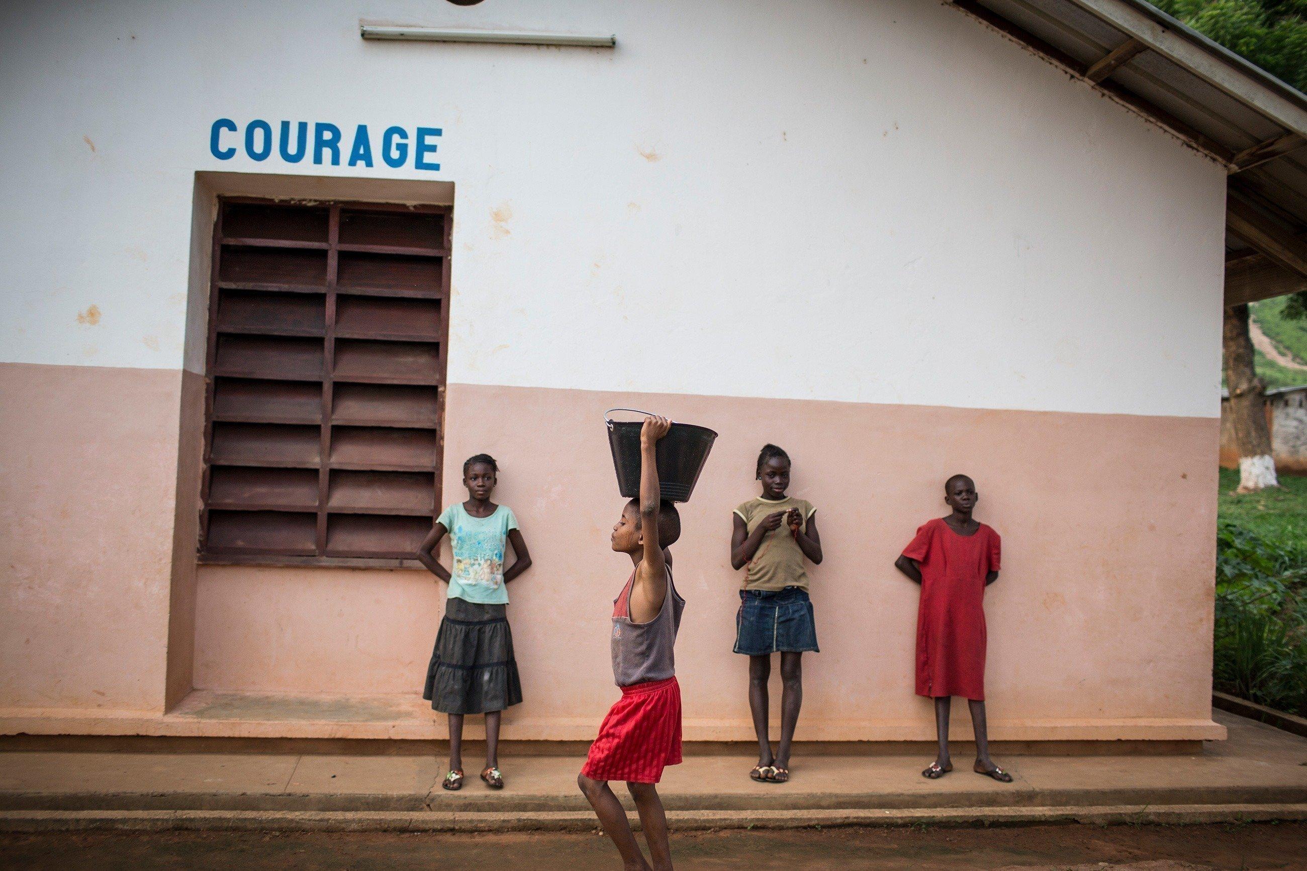 Vier Kinder stehen vor einem SOS-Kinderdorf Gebäude.