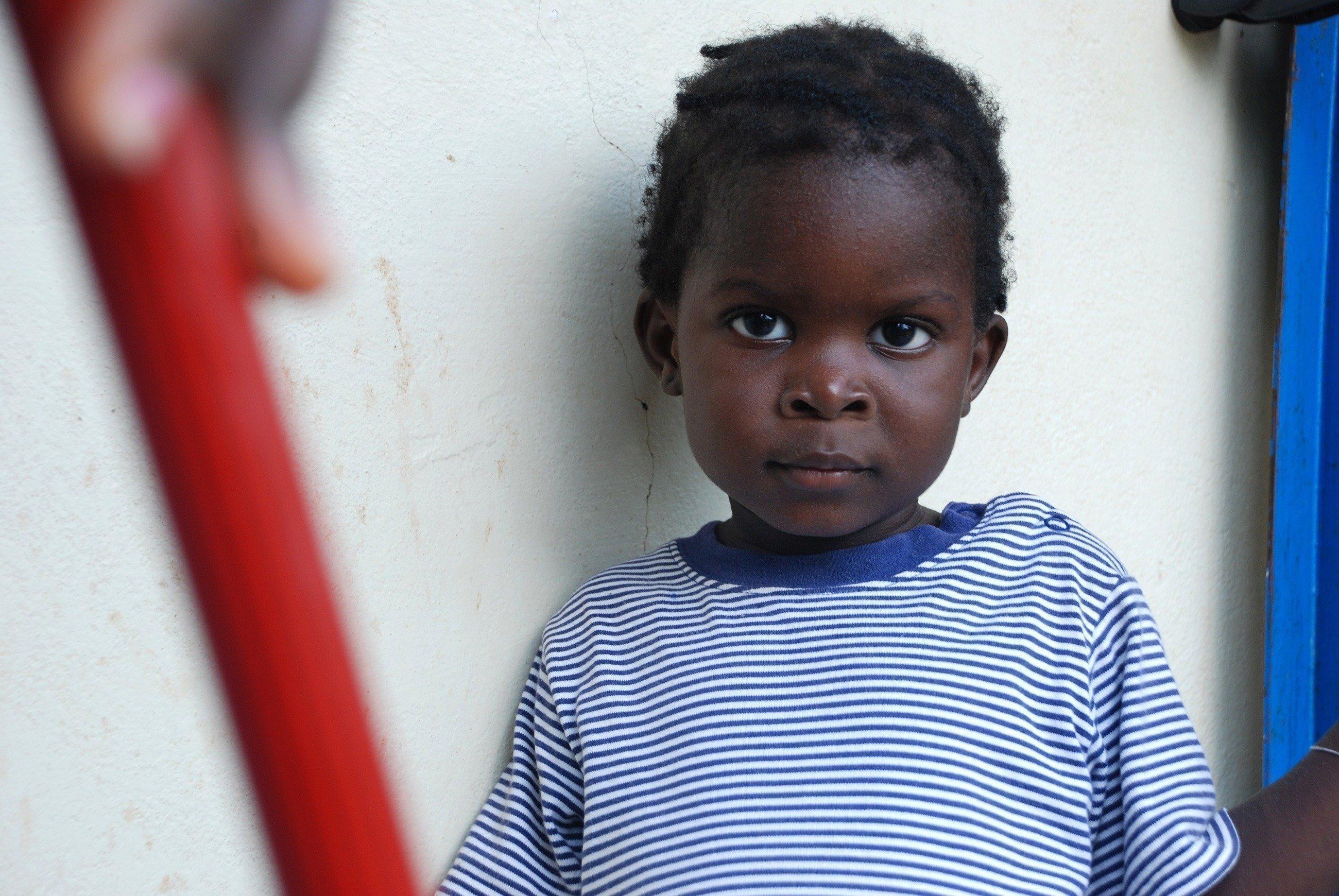 Ein kleiner Junge steht vor einer weißen Wand.