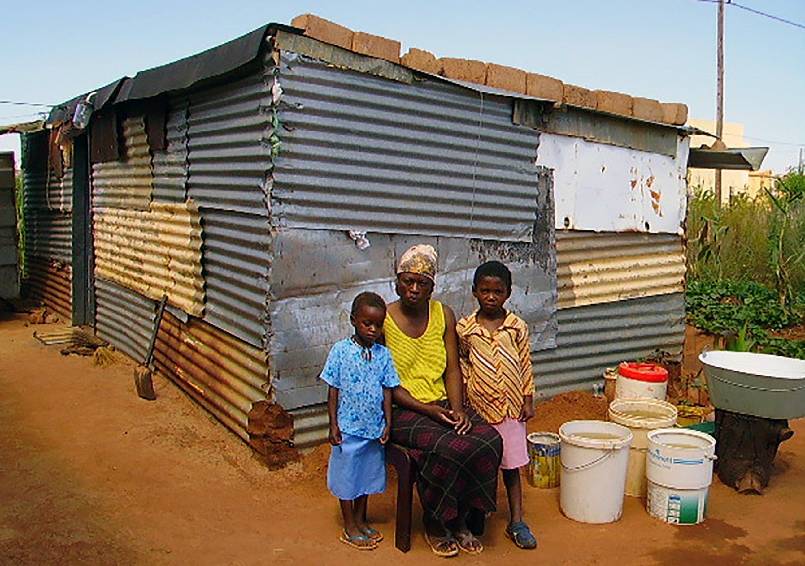 Eine afrikanische Mutter sitzt mit ihren beiden Kindern vor Ihrer Hütte aus Wellblech.