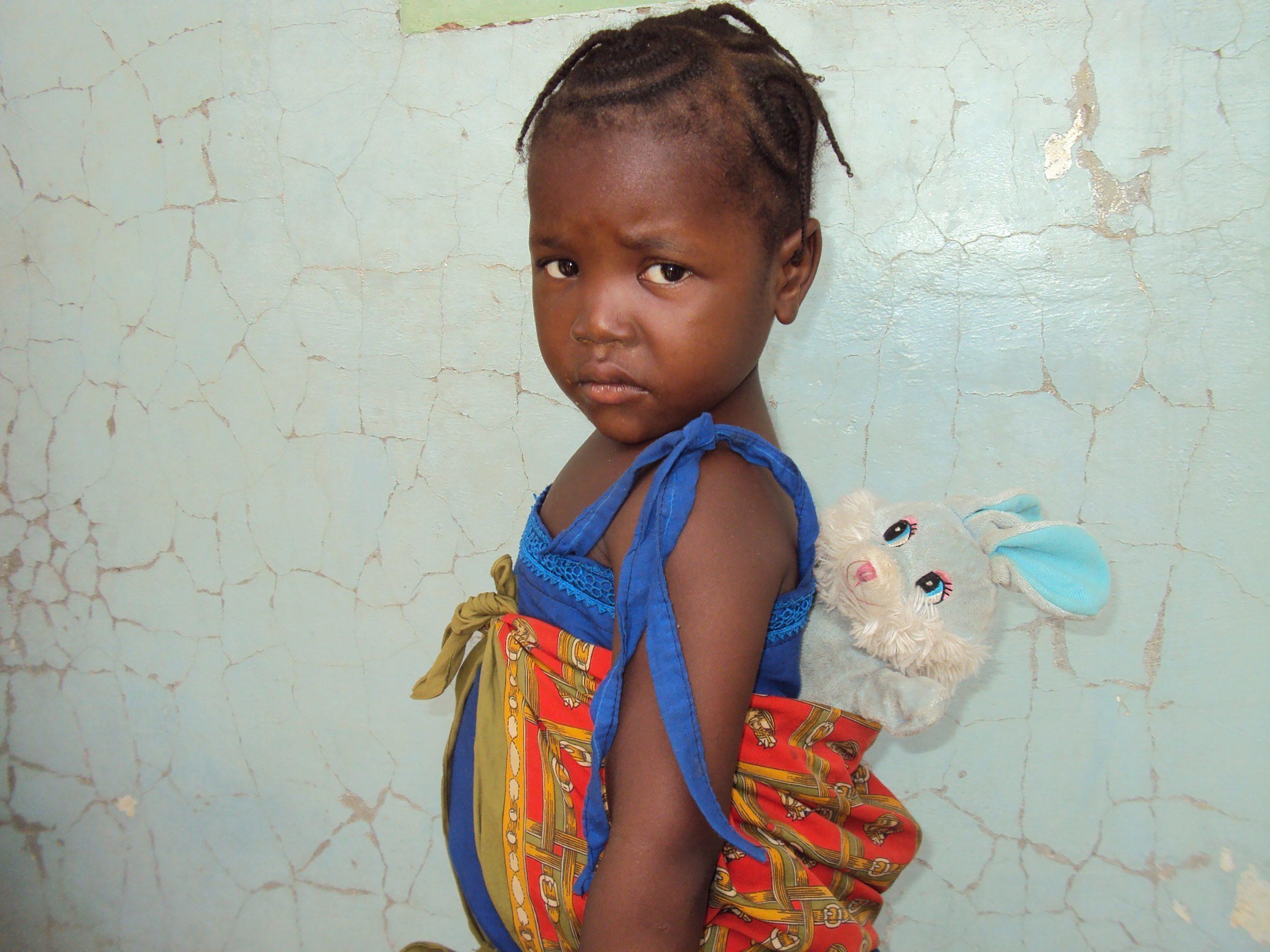 Kleines afrikanisches Mädchen mit einem Stofftier im Rucksack auf ihrem Rücken schaut traurig.