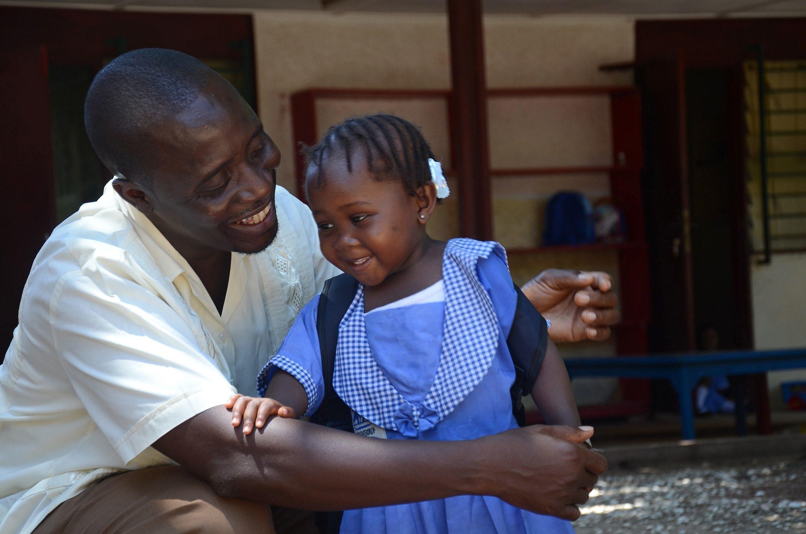 Afrikanischer Lehrer mit Schülerin im SOS-Kinderdorf.