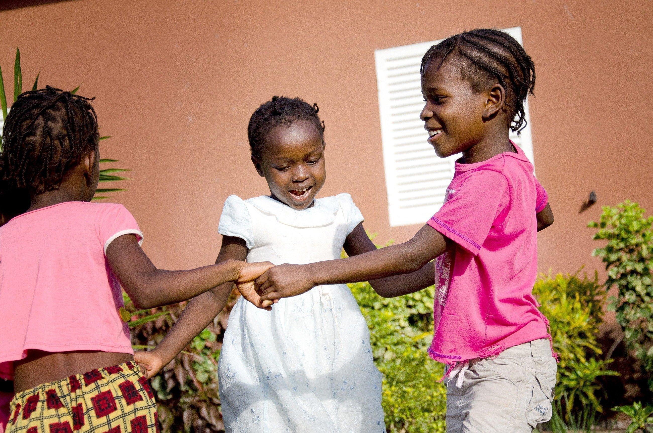 Drei Mädchen tanzen im Kreis.
