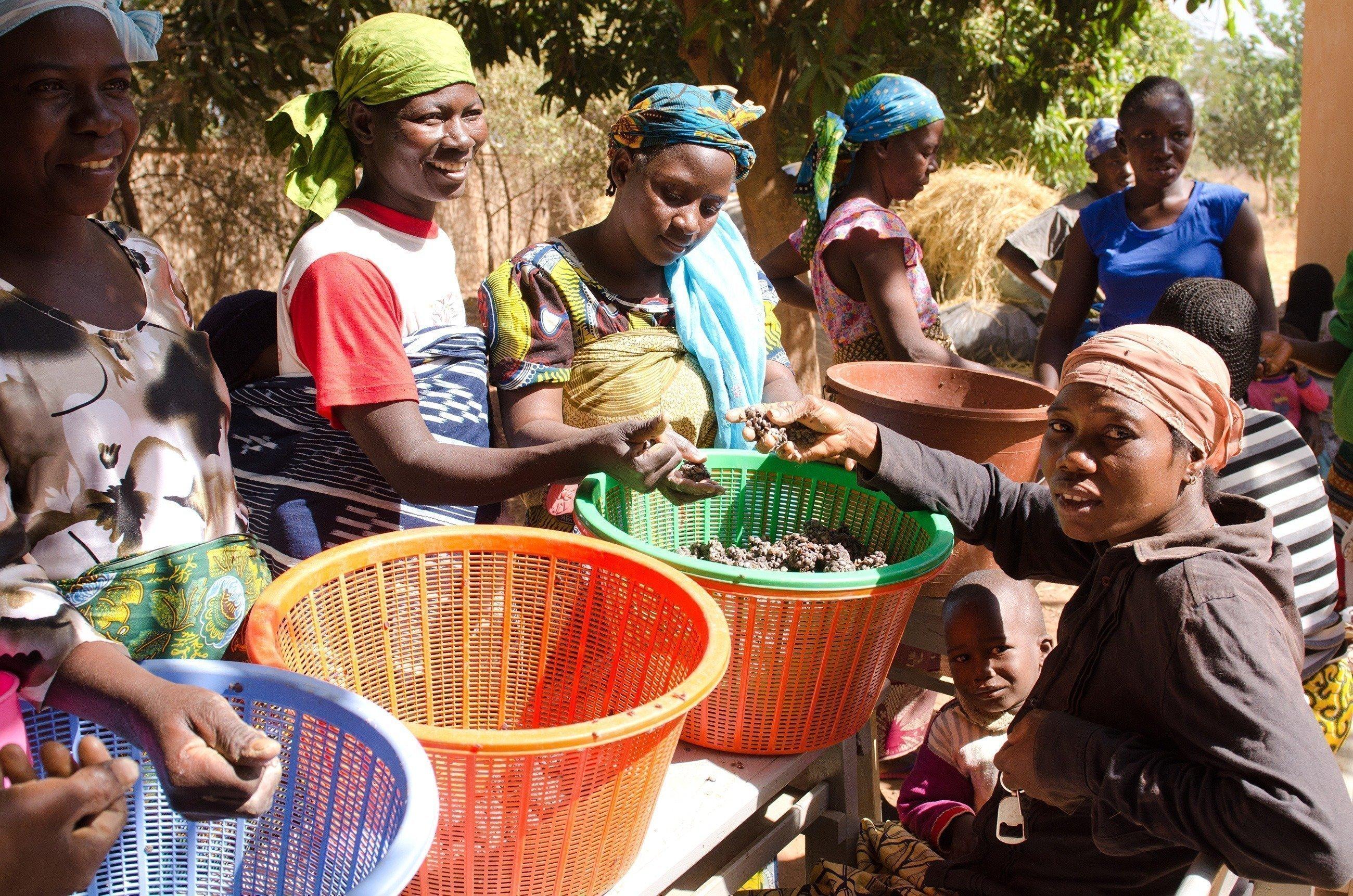 Eine Gruppe Frauen mit Körben voll Gemüse.