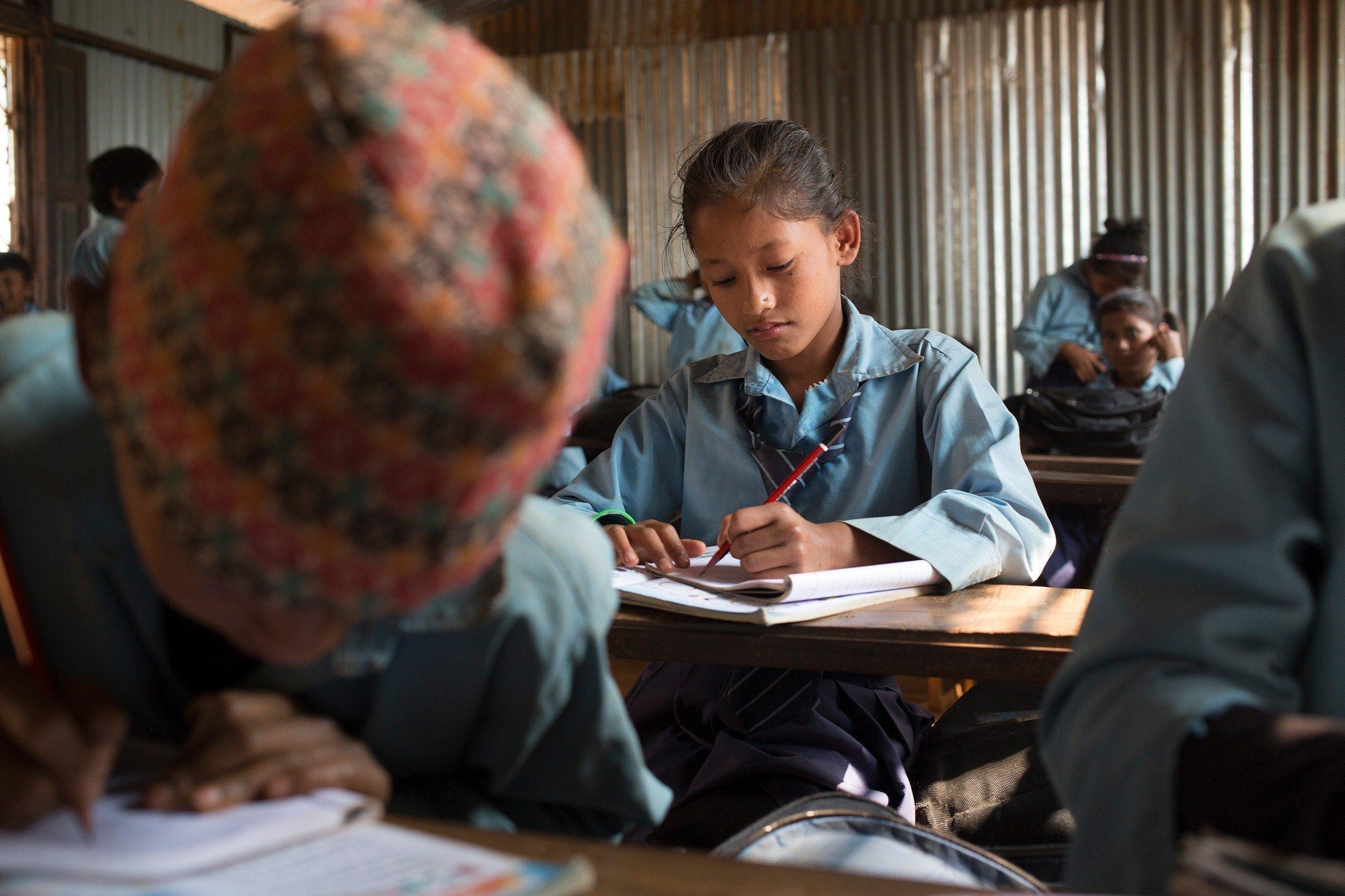 Mädchen aus Nepal sitzt in der Schule und schreibt in ihr Heft.