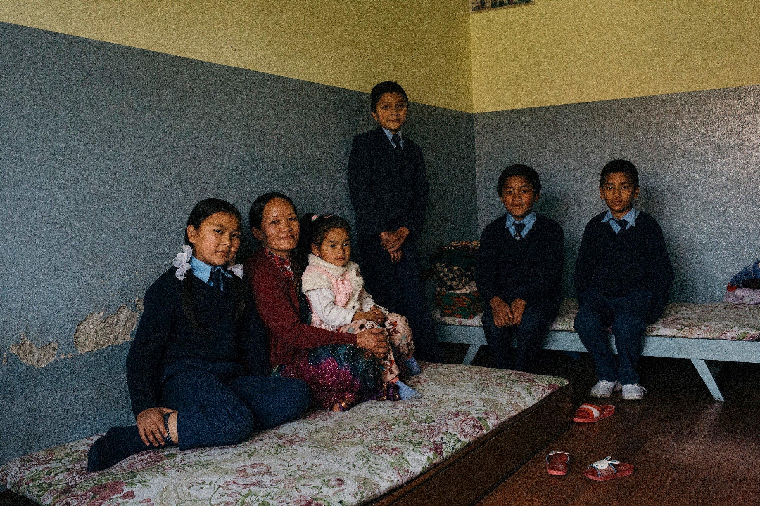 Eine Familie sitzt in einem Raum auf provisorischen Betten.