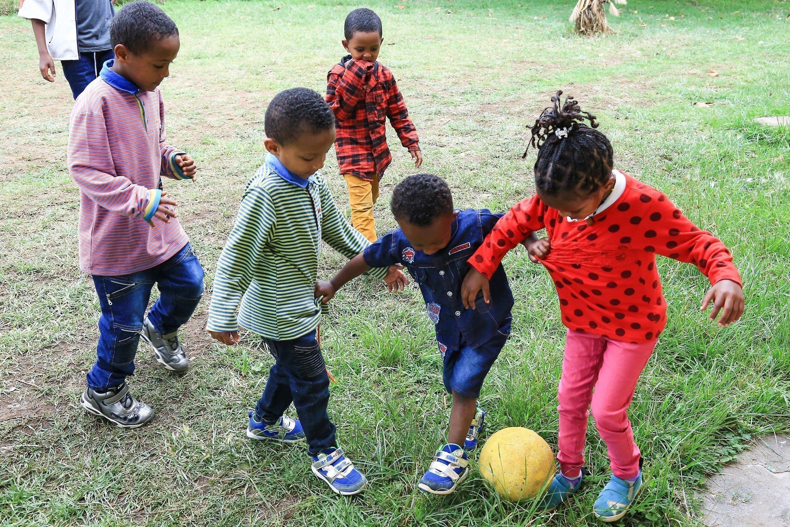 Afrikanische Kinder spielen Fußball.