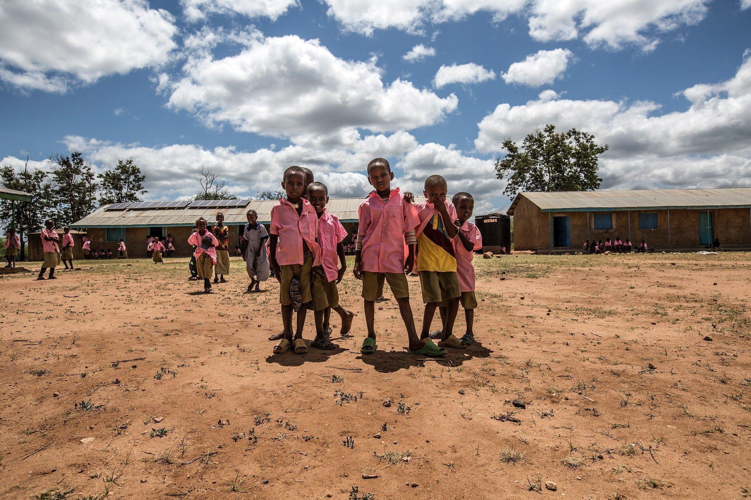 Schuljungen in rosa Hemden vor ihrer Schule.