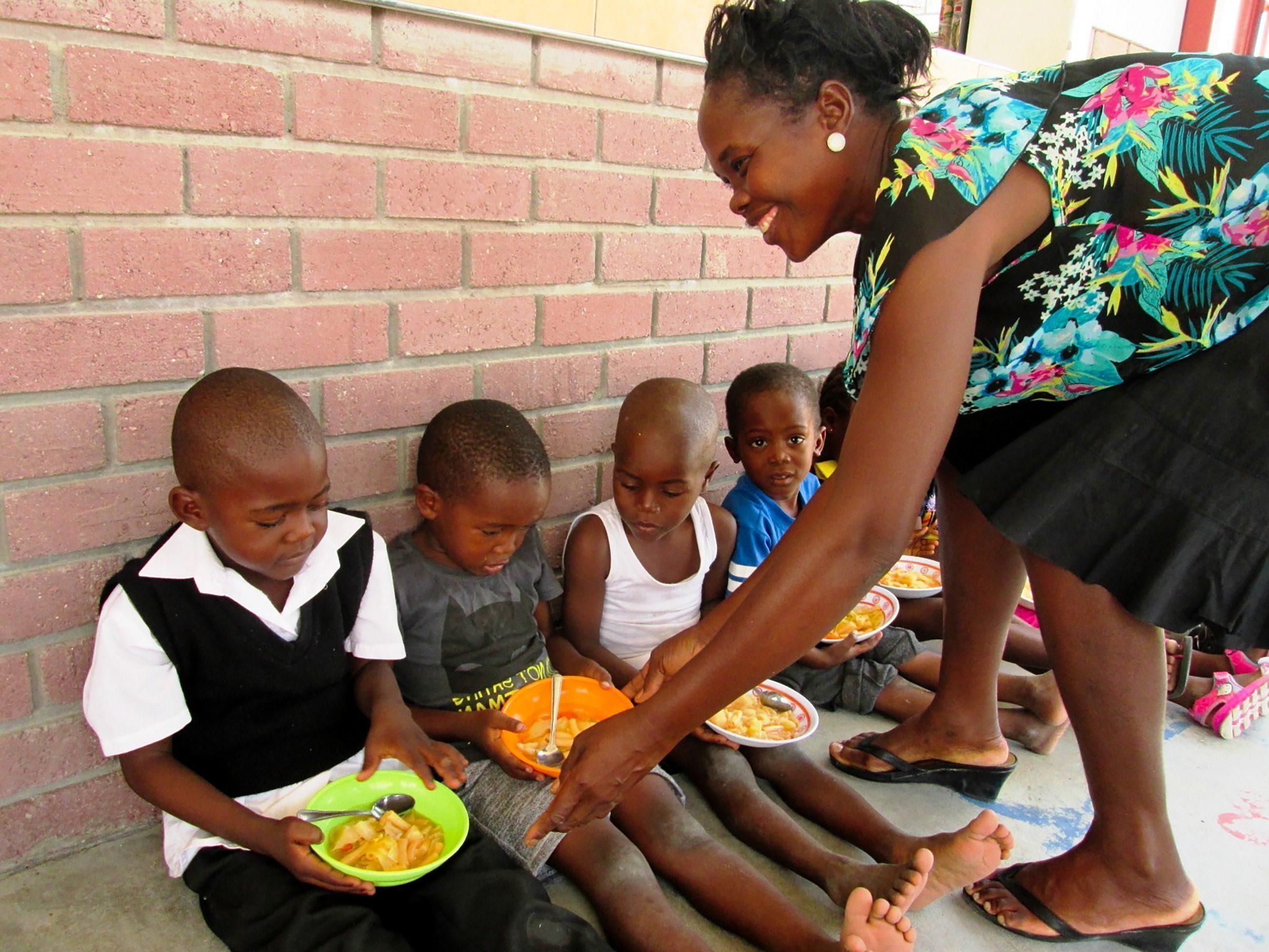 Eine SOS-Kinderdorf Mutter versorgt Kinder mit Essen.