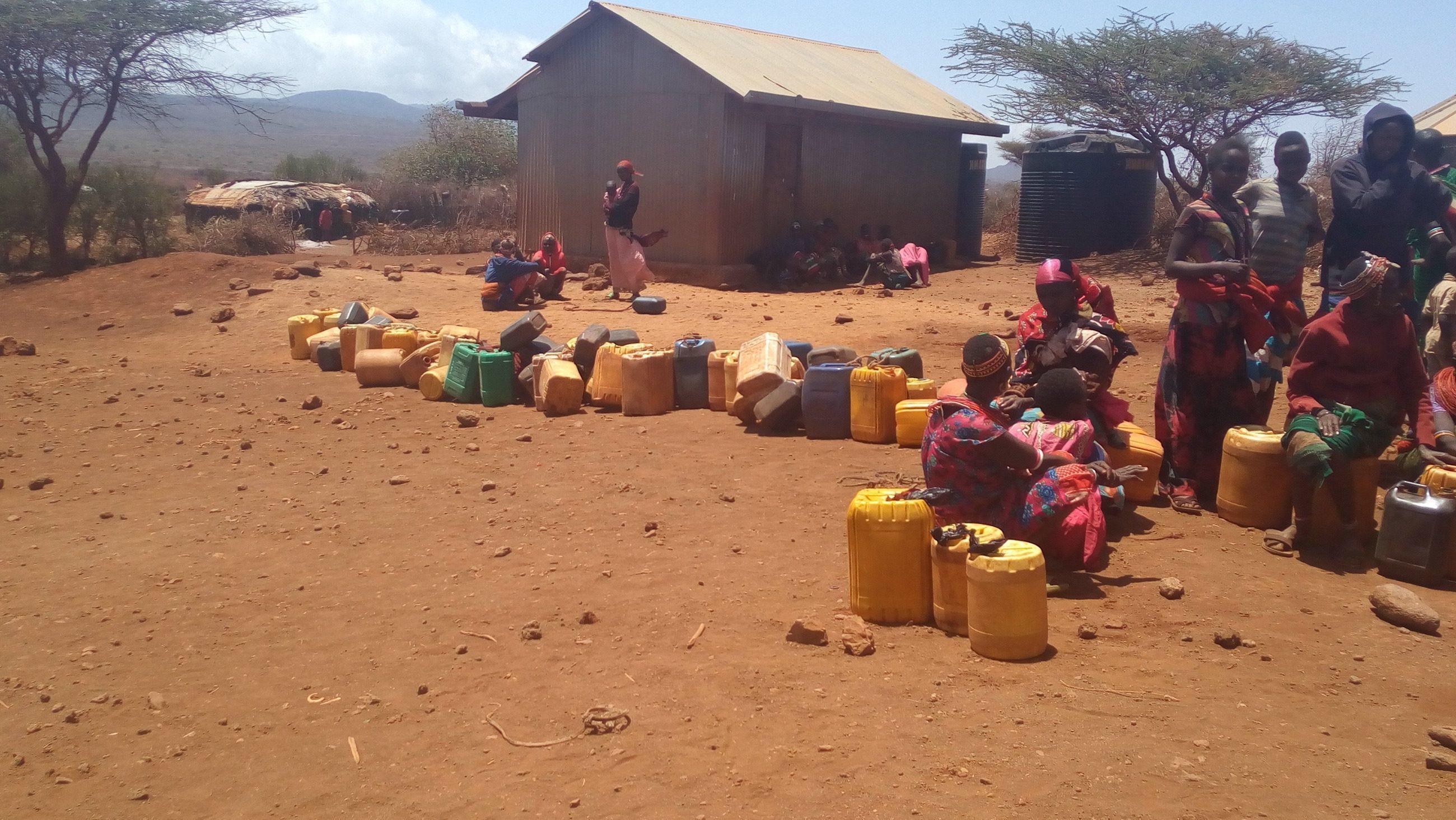 Afrikanische Frauen mit ihren Wasserträgern.