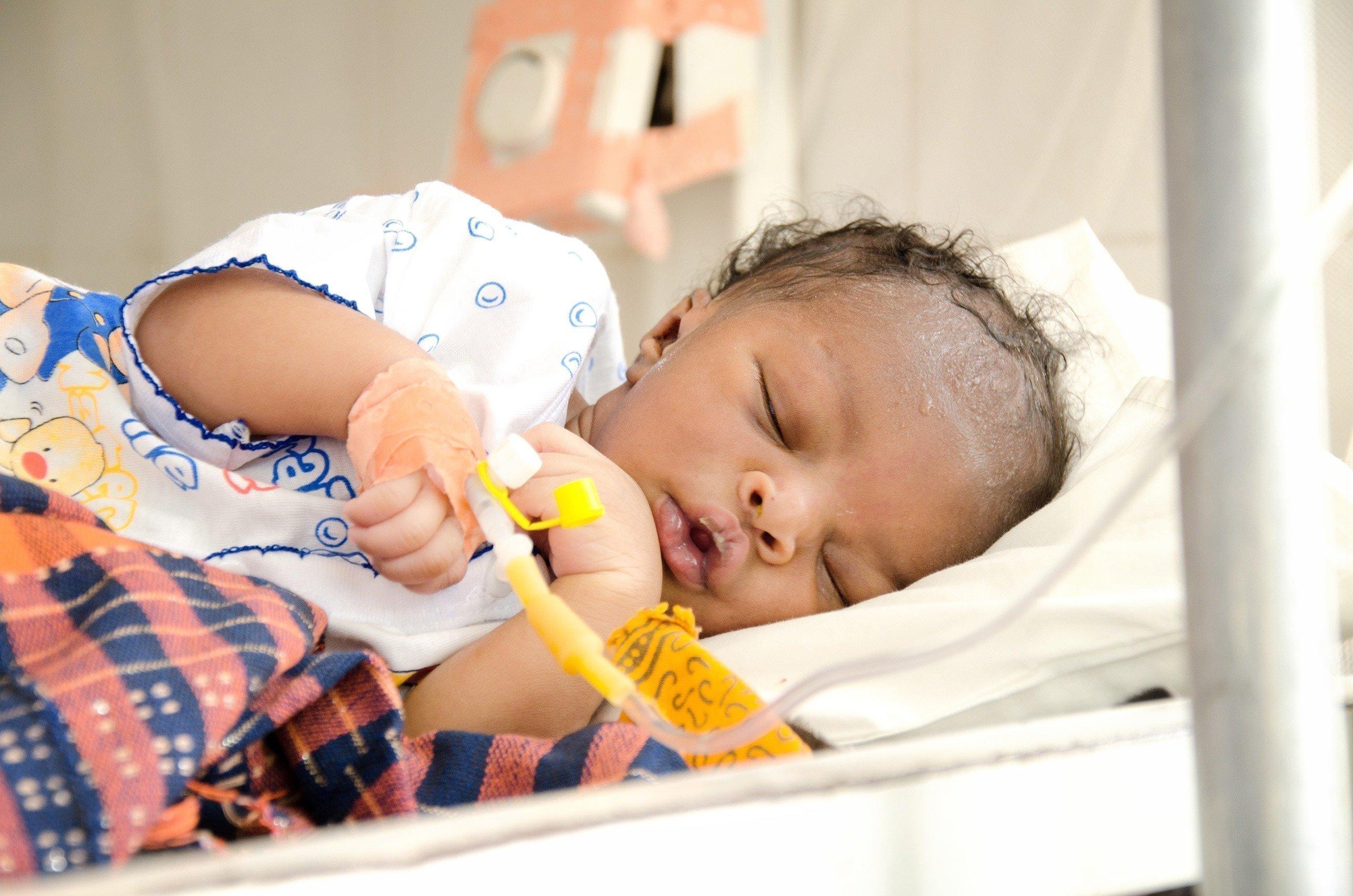 Kleines Baby schläft mit einem intravenösem Zugang an der Hand.