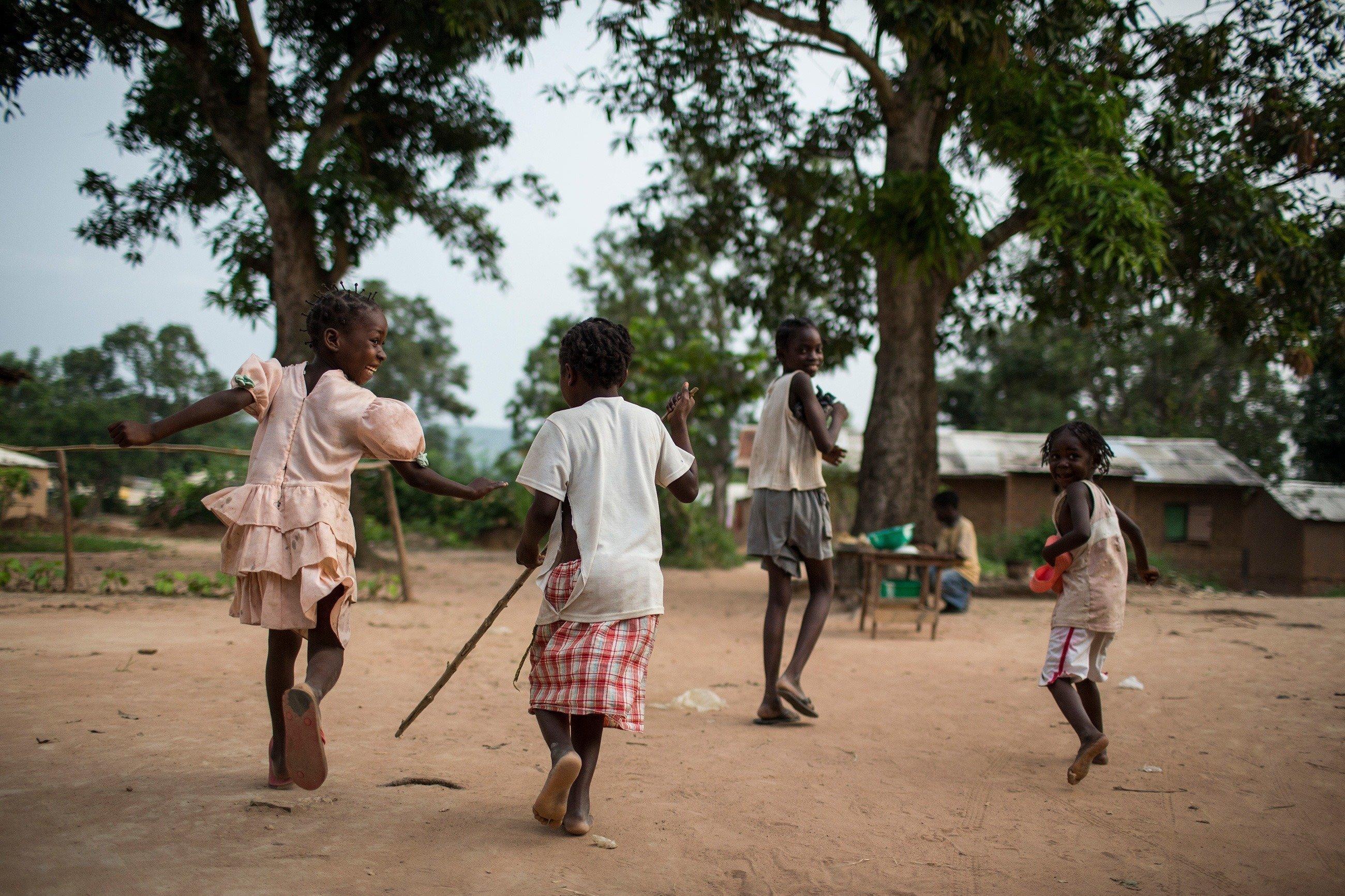 Afrikanische Kinder spielen fangen.
