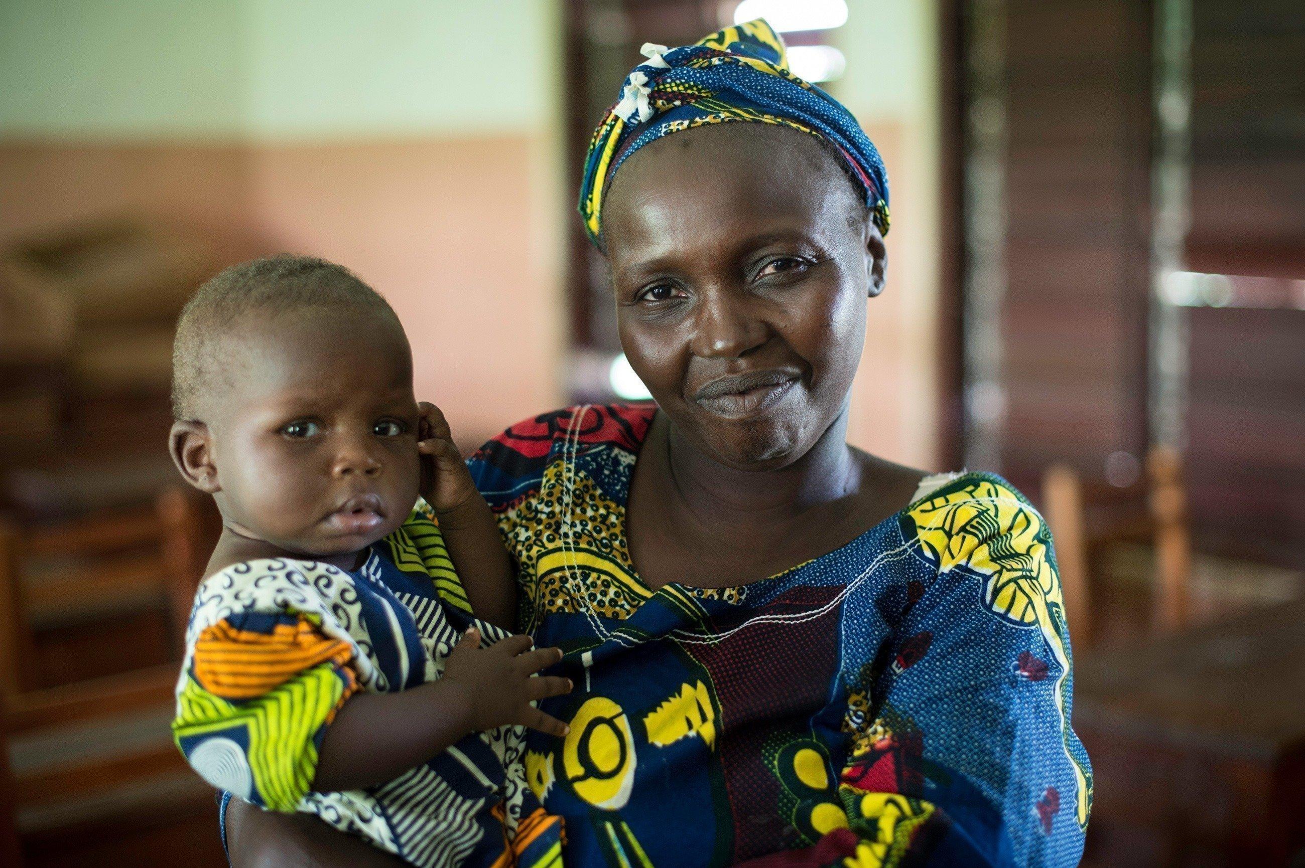 SOS-Kinderdorf Mutter mit einem Kind auf dem Arm.