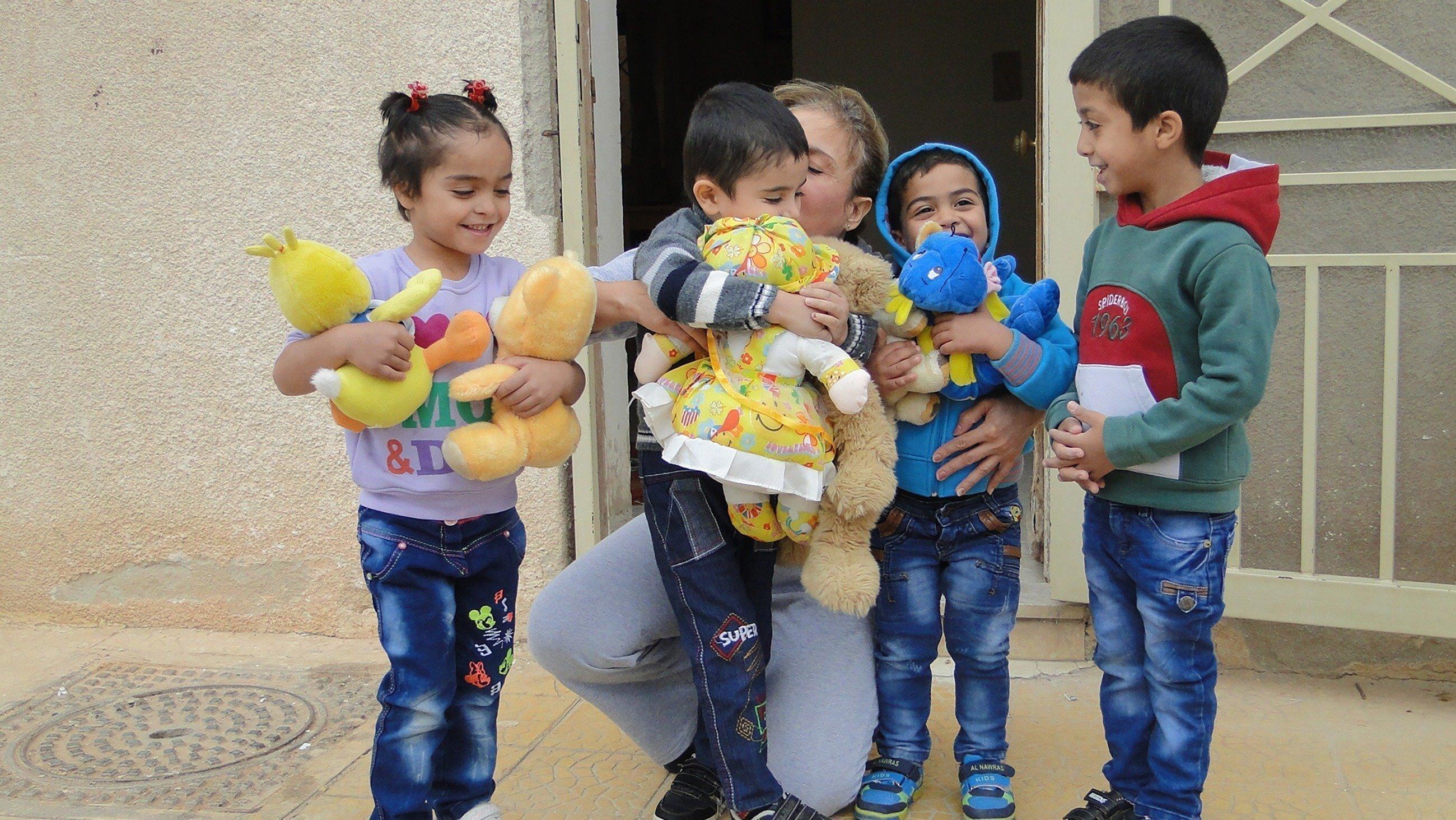 Kinder freuen sich über Kuscheltiere.