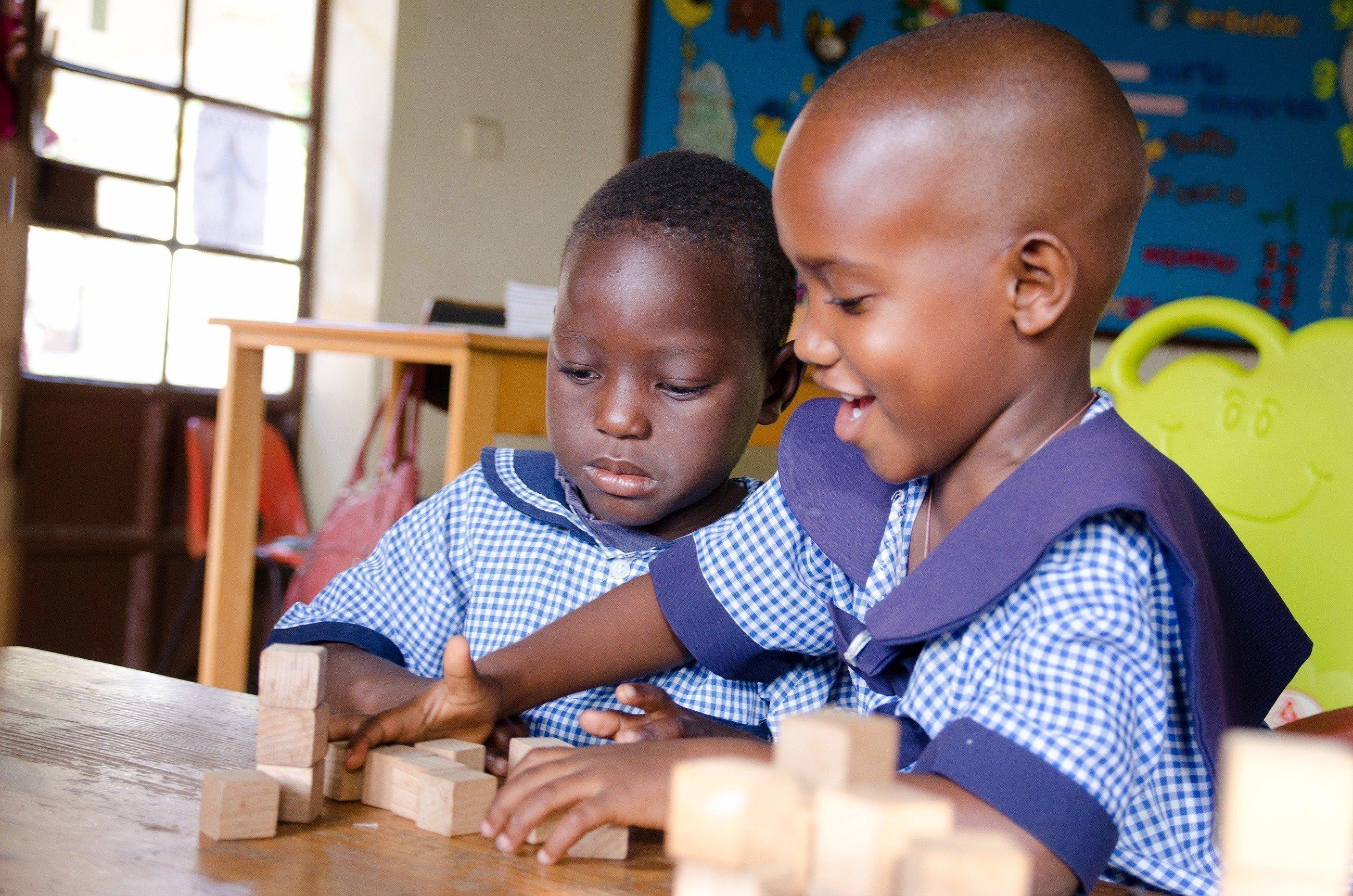 Zwei afrikanische Kinder im Kindergarten spielen mit Bauklötzen.