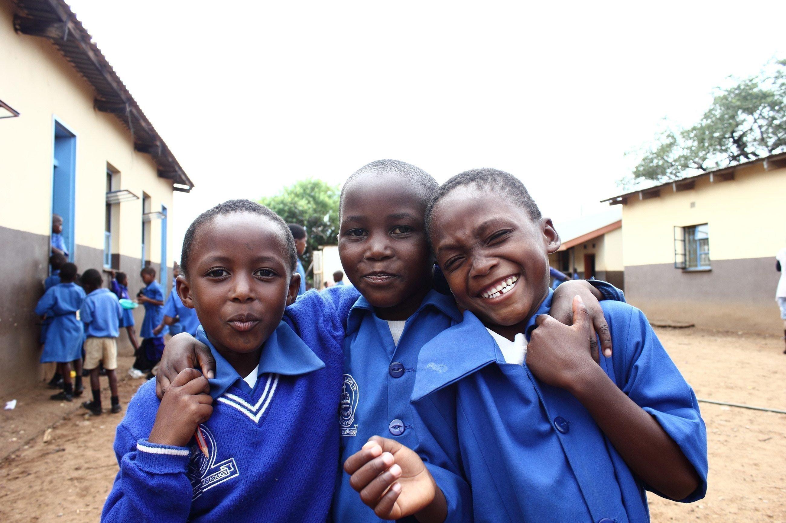 Drei Schuljungen in blauer Uniform umarmen sich.
