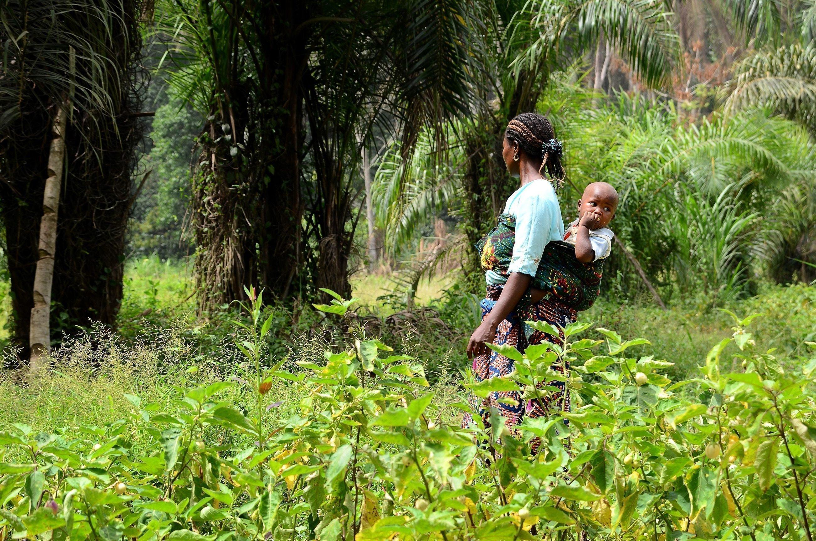 Eine Mutter trägt ihr Kind mit einem Tuch auf ihrem Rücken durch dichtes Grün.