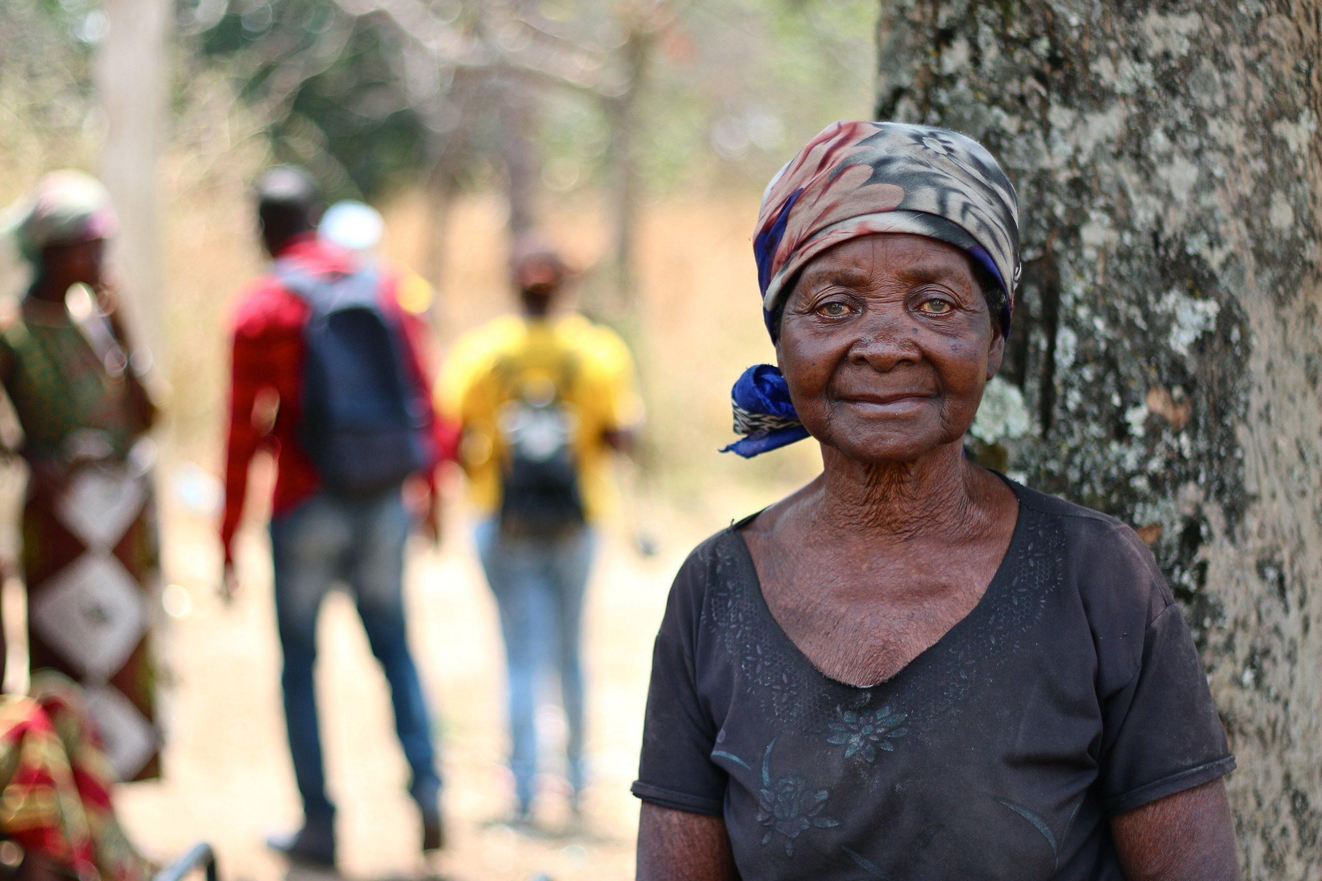 Eine ältere Frau vor einem Baum.