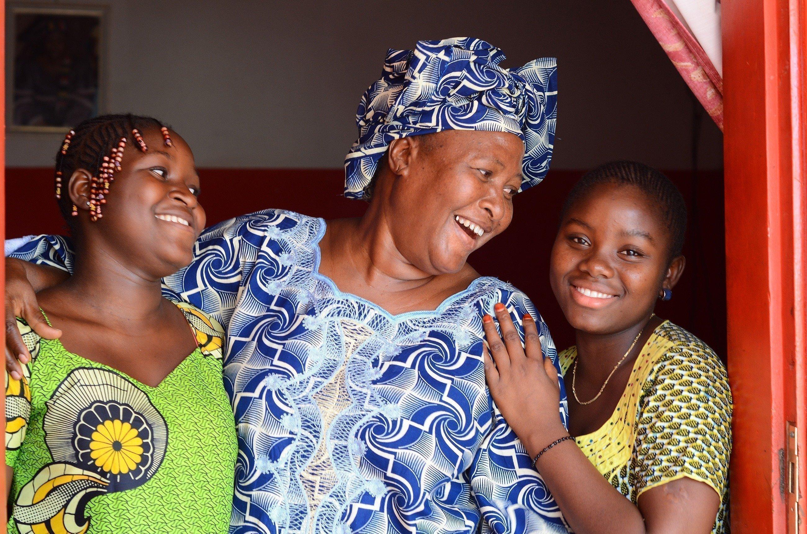 Eine Mutter lacht mit ihren beiden Töchtern.