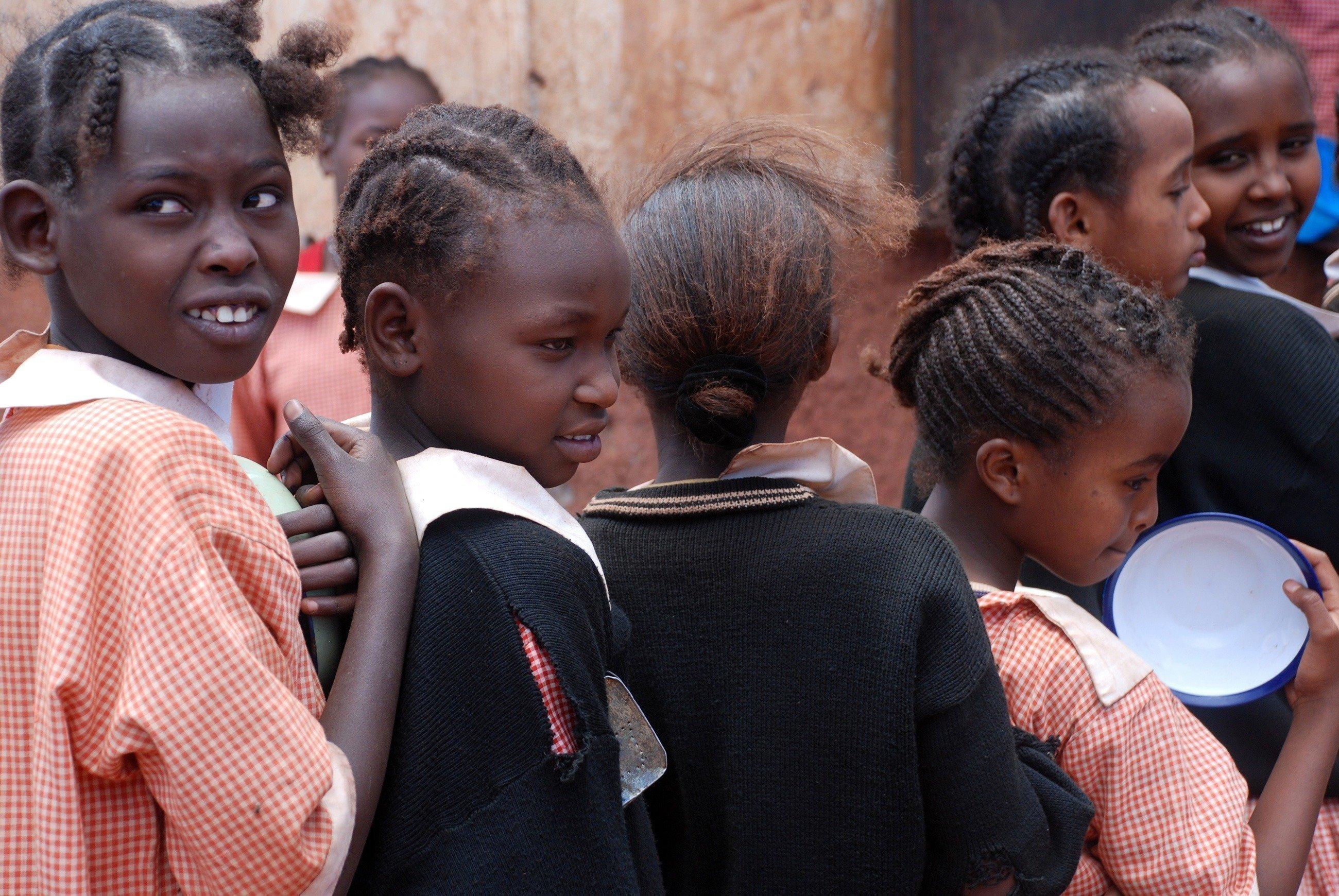 Kinder warten in einer Schlange auf ihr Essen.