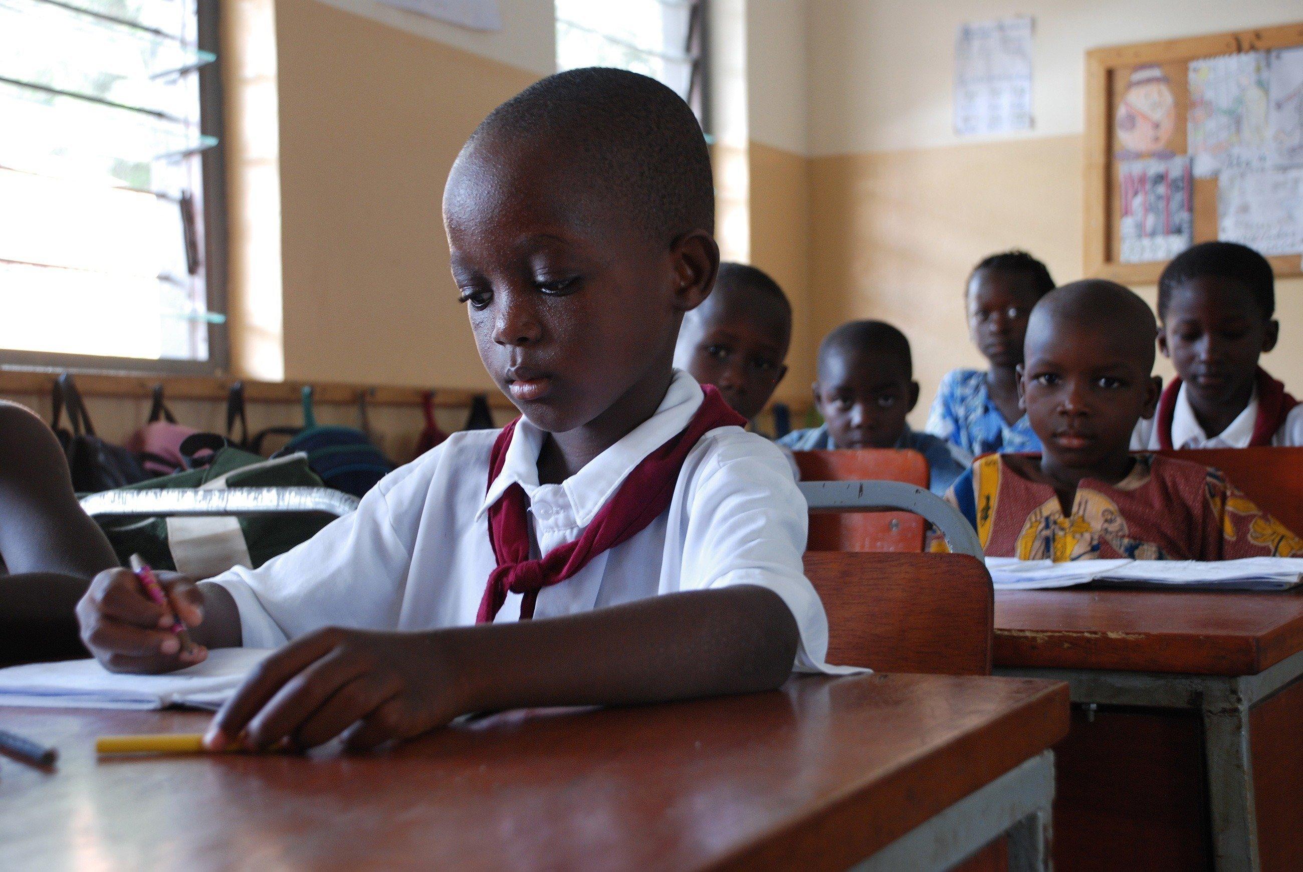 Afrikanische Schüler schreiben in einer Klassenzimmer.
