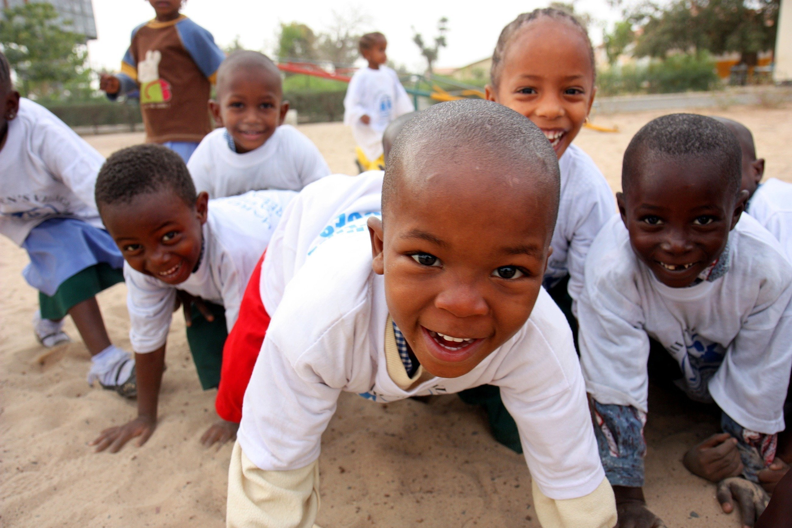 Eine Gruppe afrikanischer Kinder krabbelt im Sand.